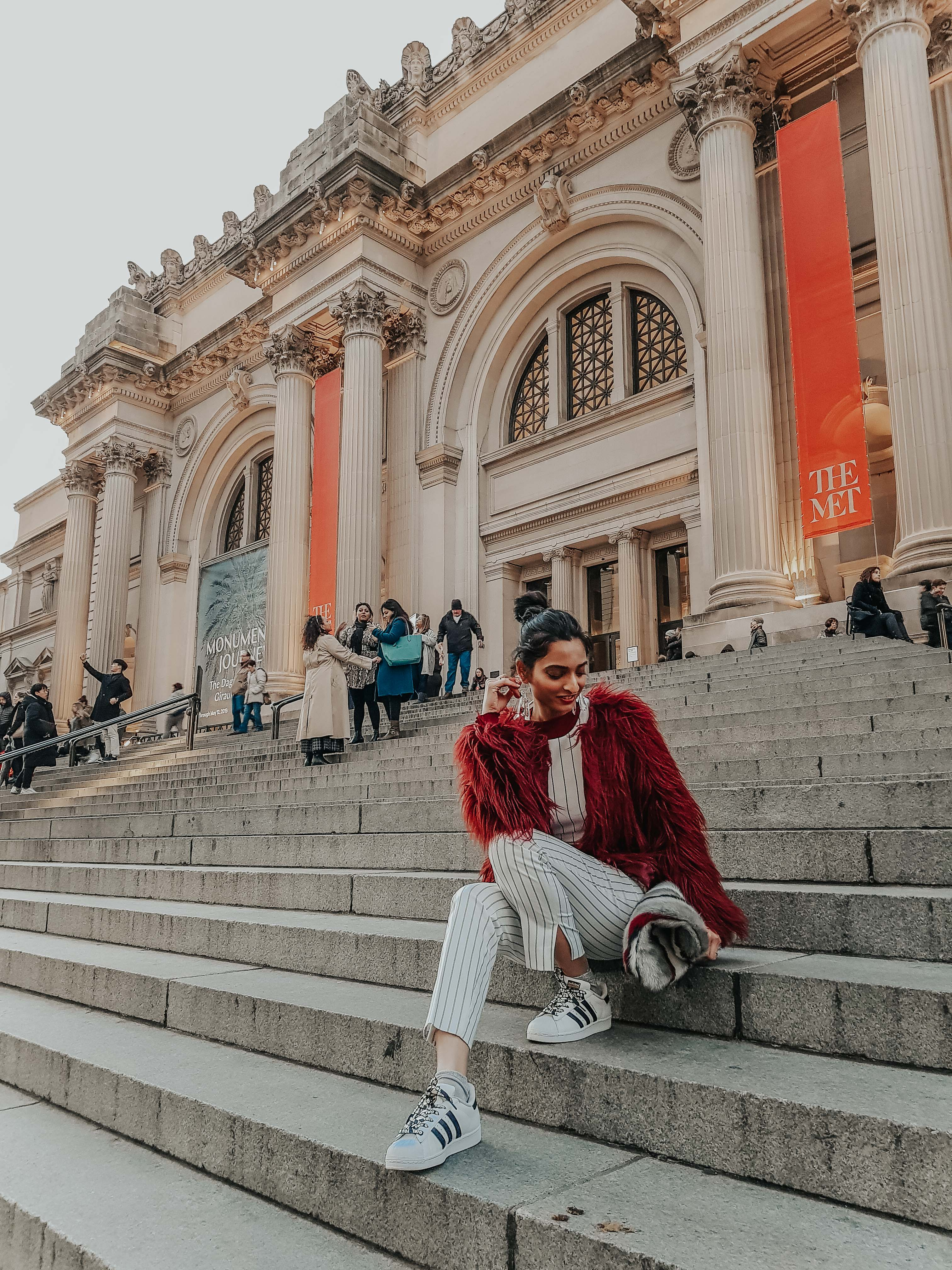 girl wearing white pinstriped pant and top set with maroon faux fur jacket sitting on the steps of the MET museum in new york city