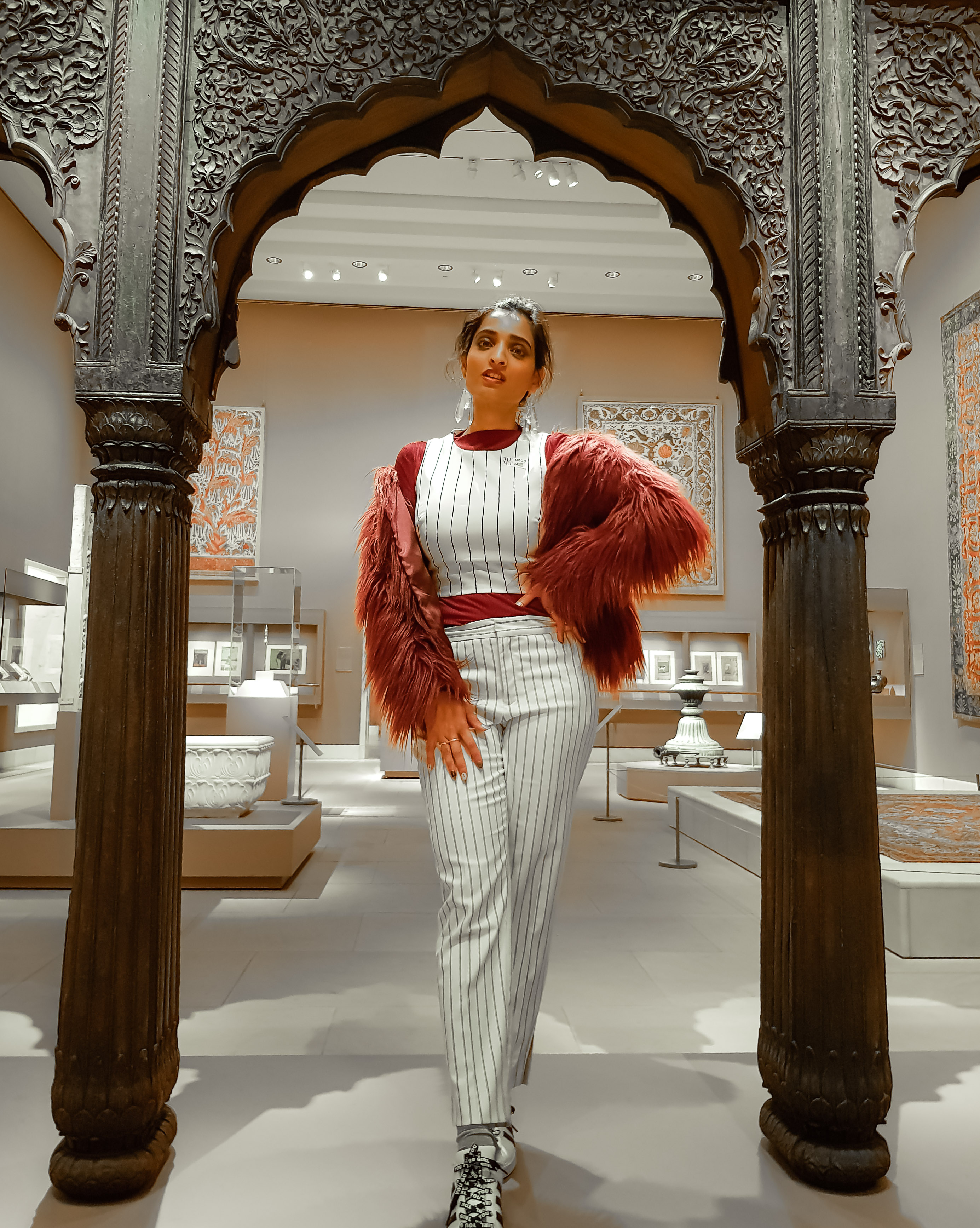 girl wearing white pinstriped pant and top set with maroon faux fur jacket inside the MET museum in new york city