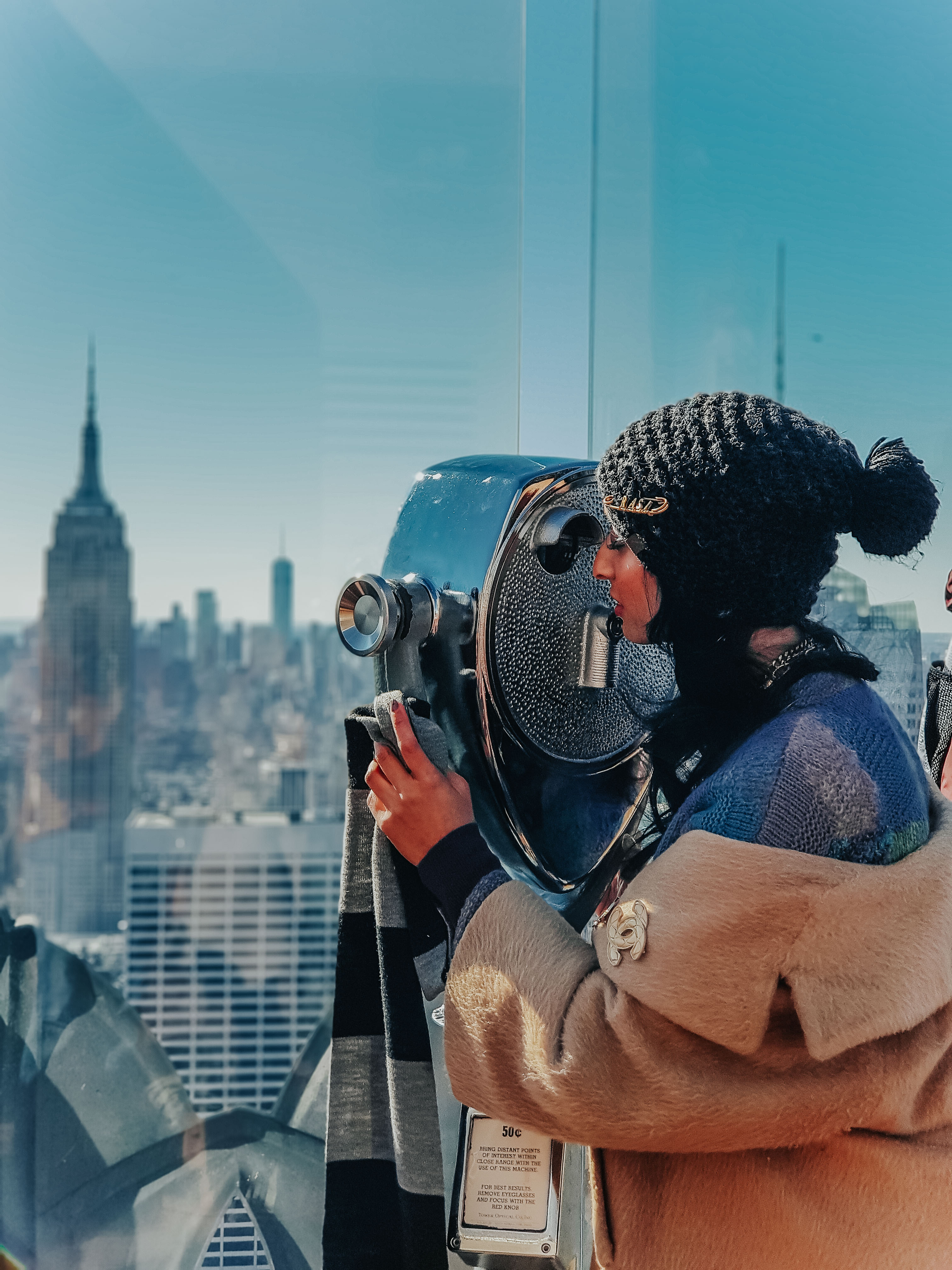 girl wearing nude coloured coat and a beanie cap at the top of the rockerfeller centre in new york city looking through tower viewer