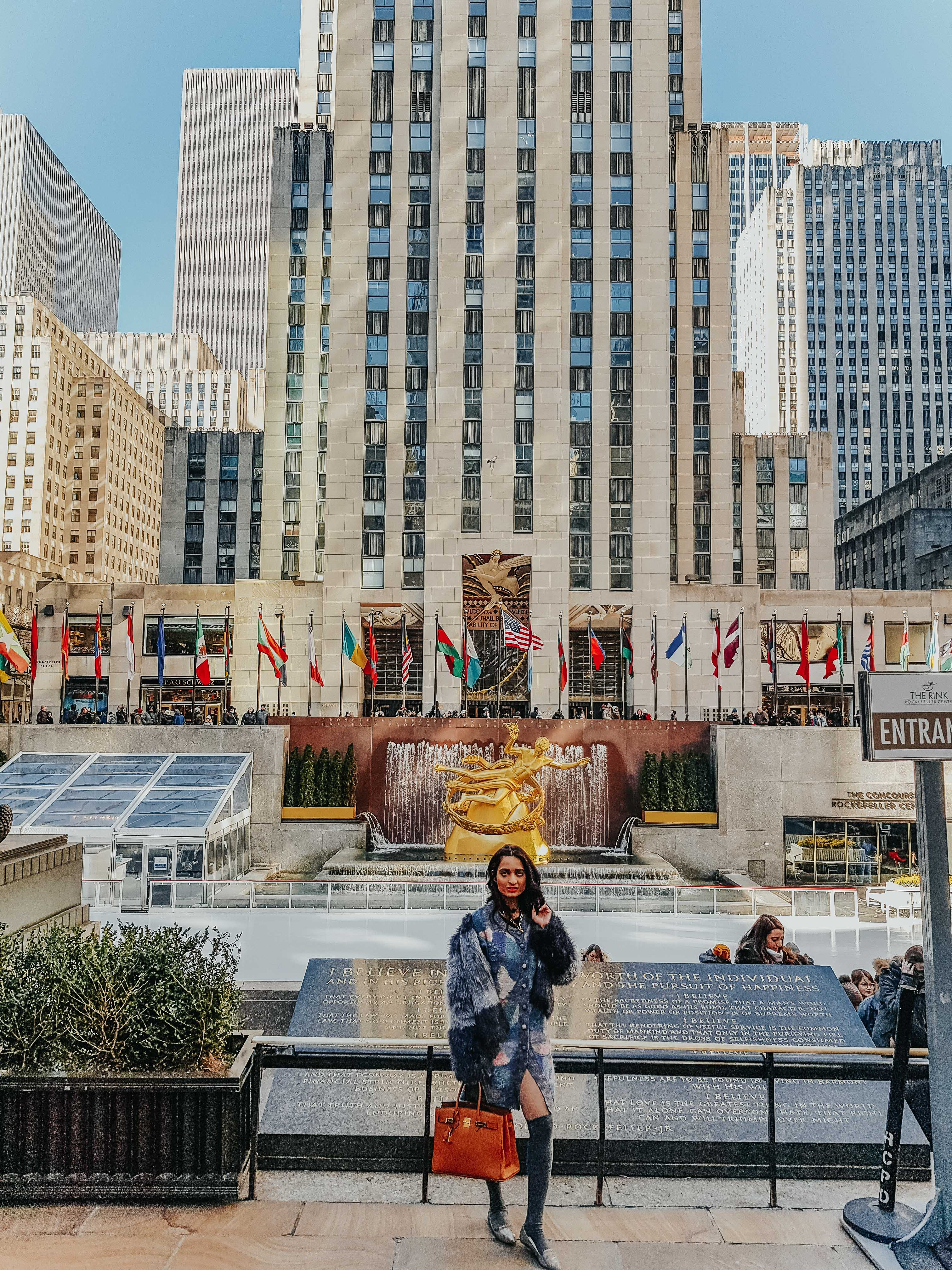 girl standing at the bottom of the rockerfeller centre in new york city