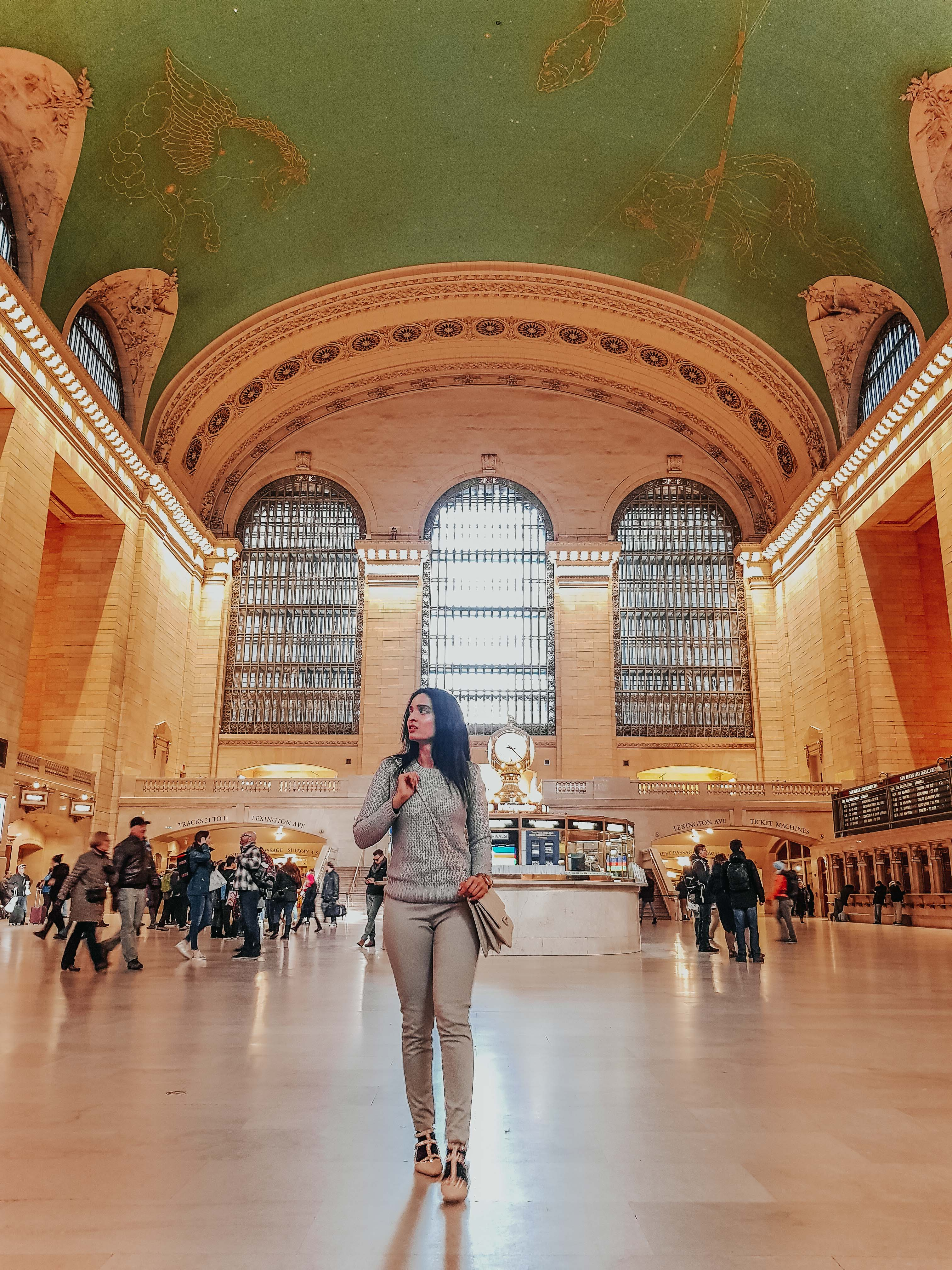 girl standing inside the grand central train station as part of new york travel guide