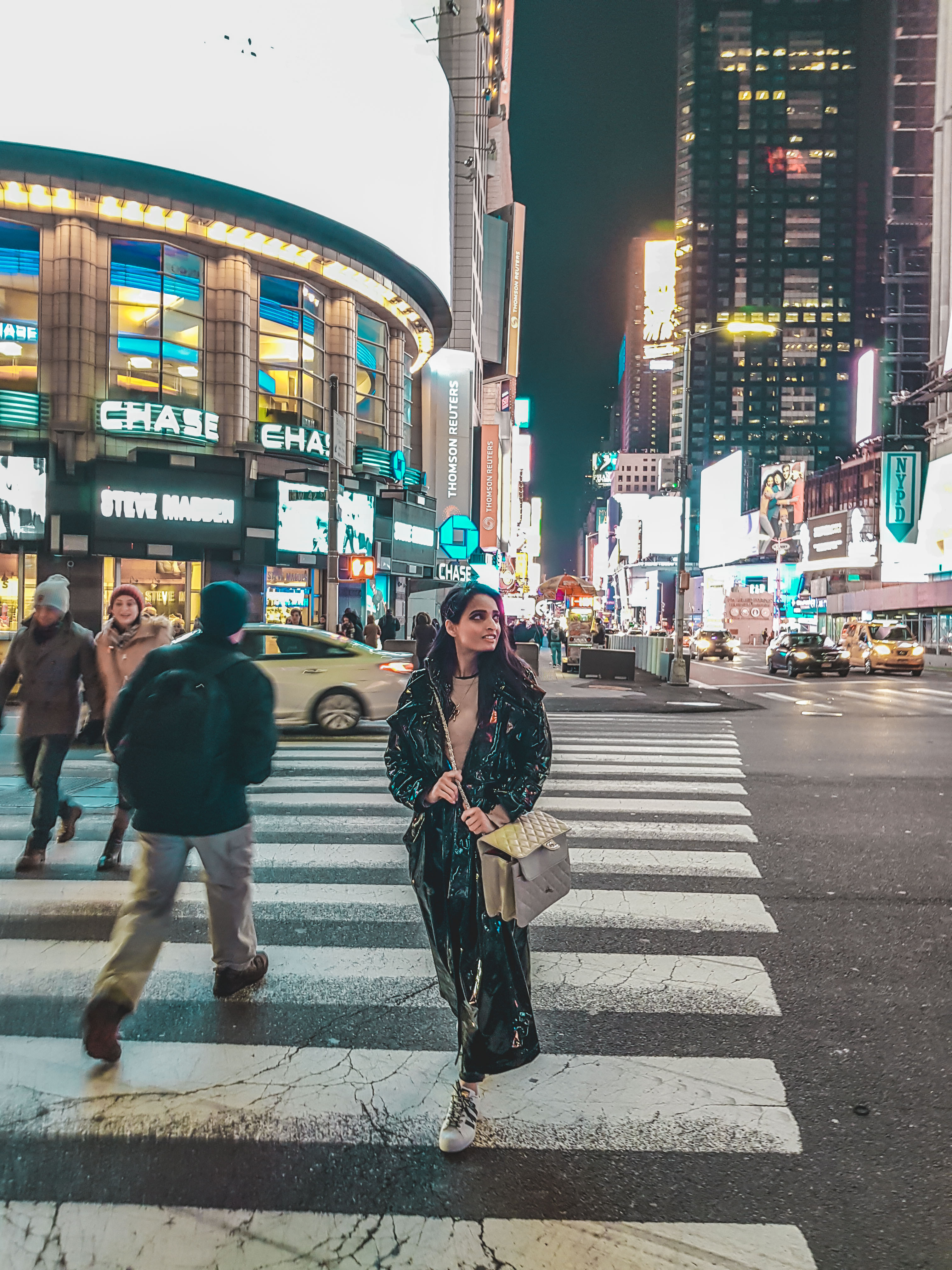 girl crossing the street at night at Times Square in new york city