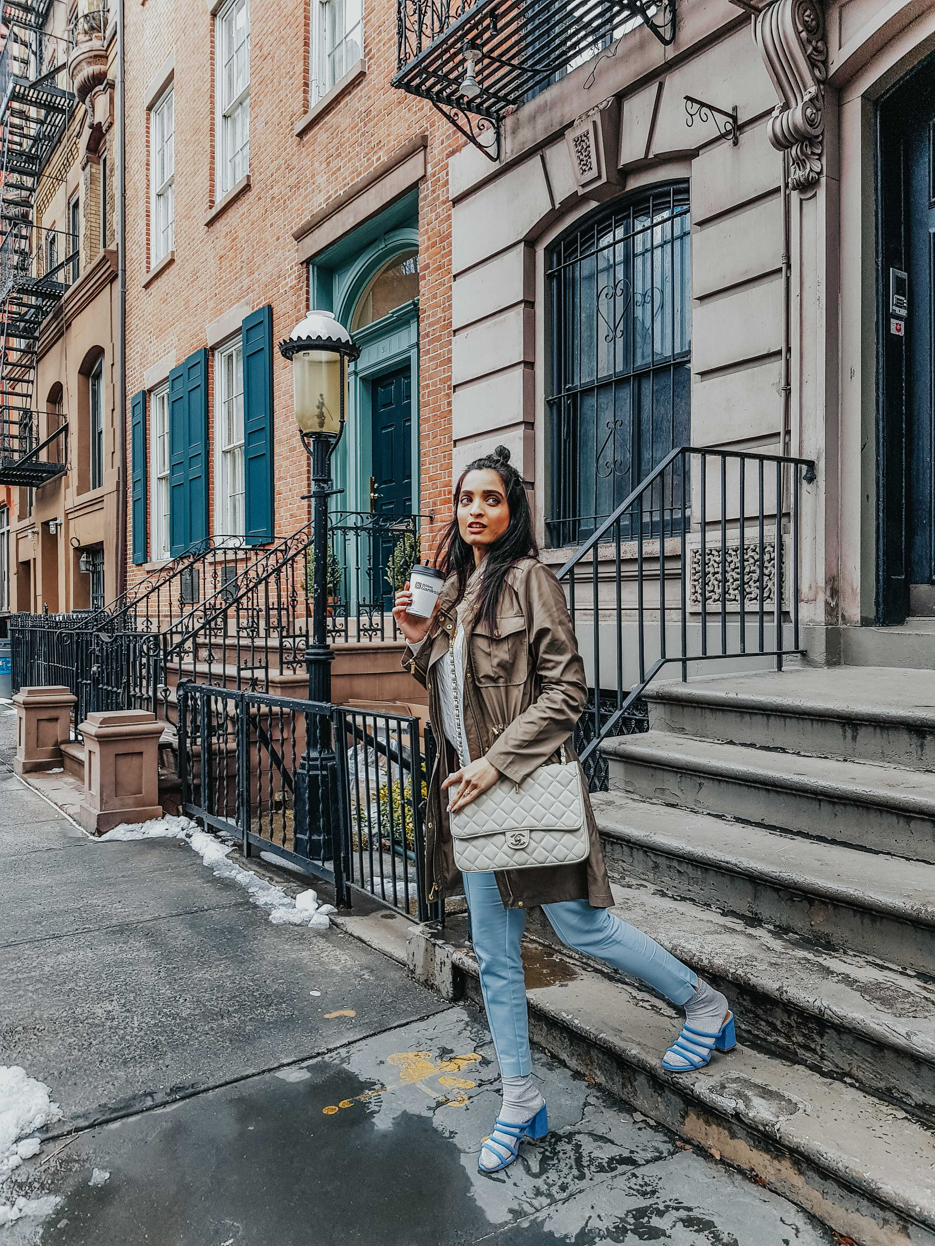 girl holding coffee and climbing down the stairs in new york city