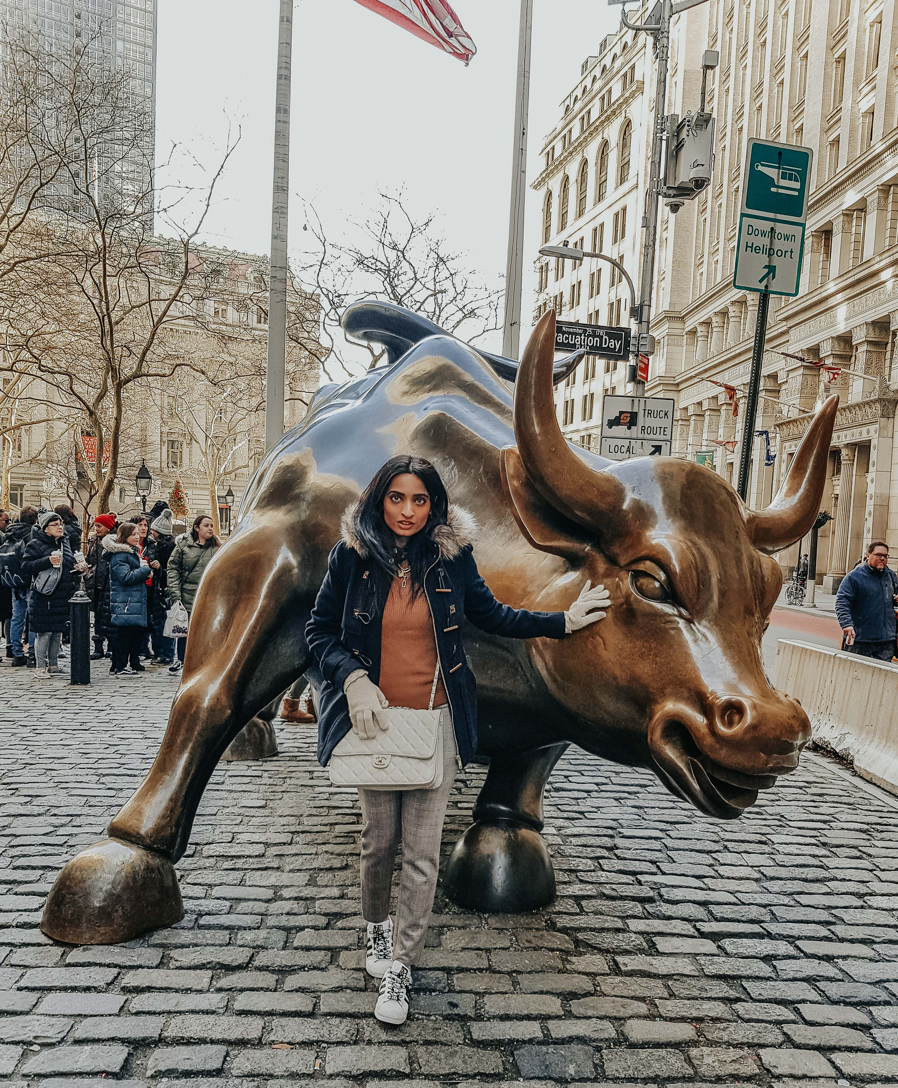 girl standing with the metallic brown bull statue at wall street in new york city