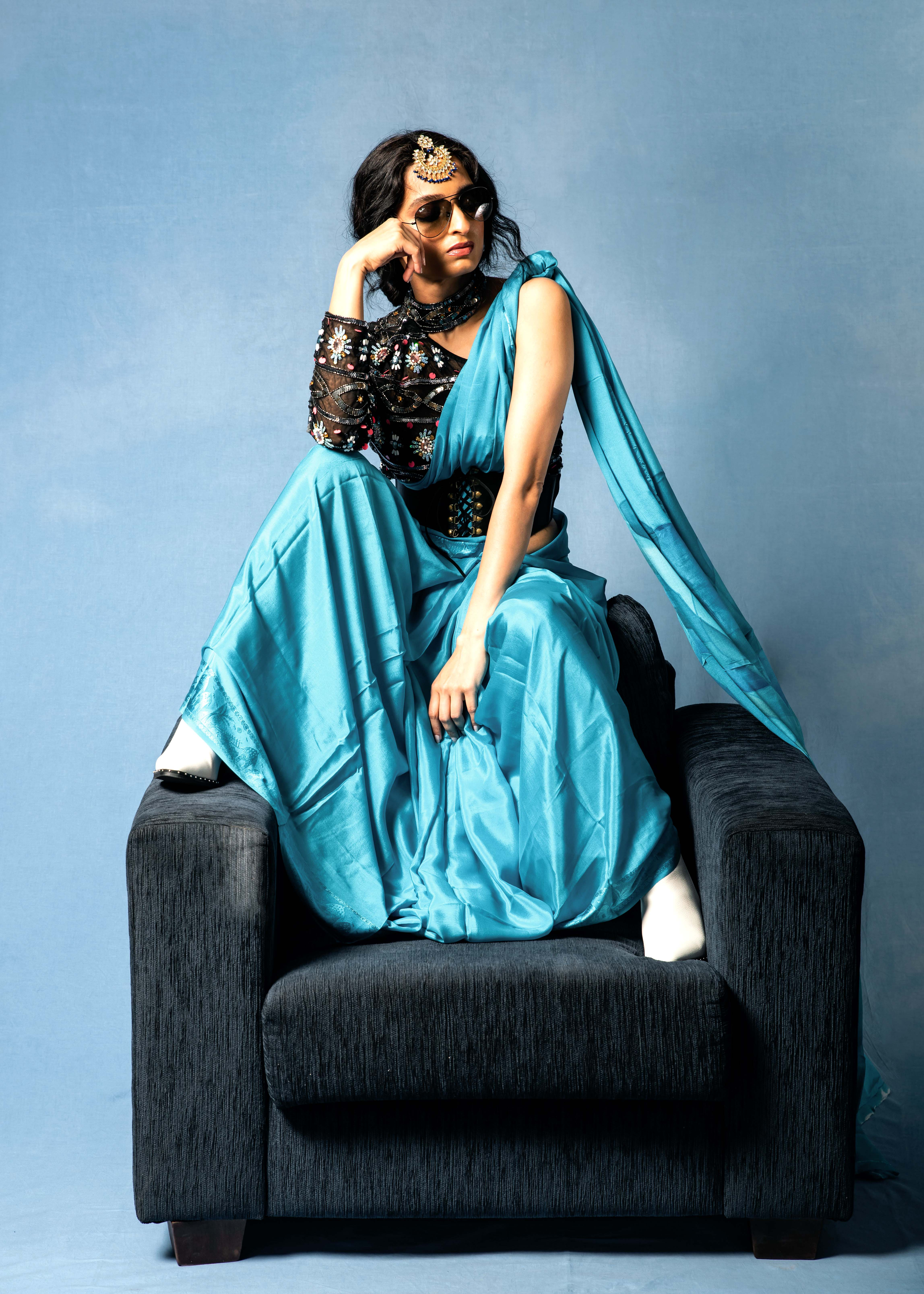 Blue silk saree indian outfit indian style with one shoulder embroidered black blouse and sunglasses and white boots sitting on an arm chair studio photograph