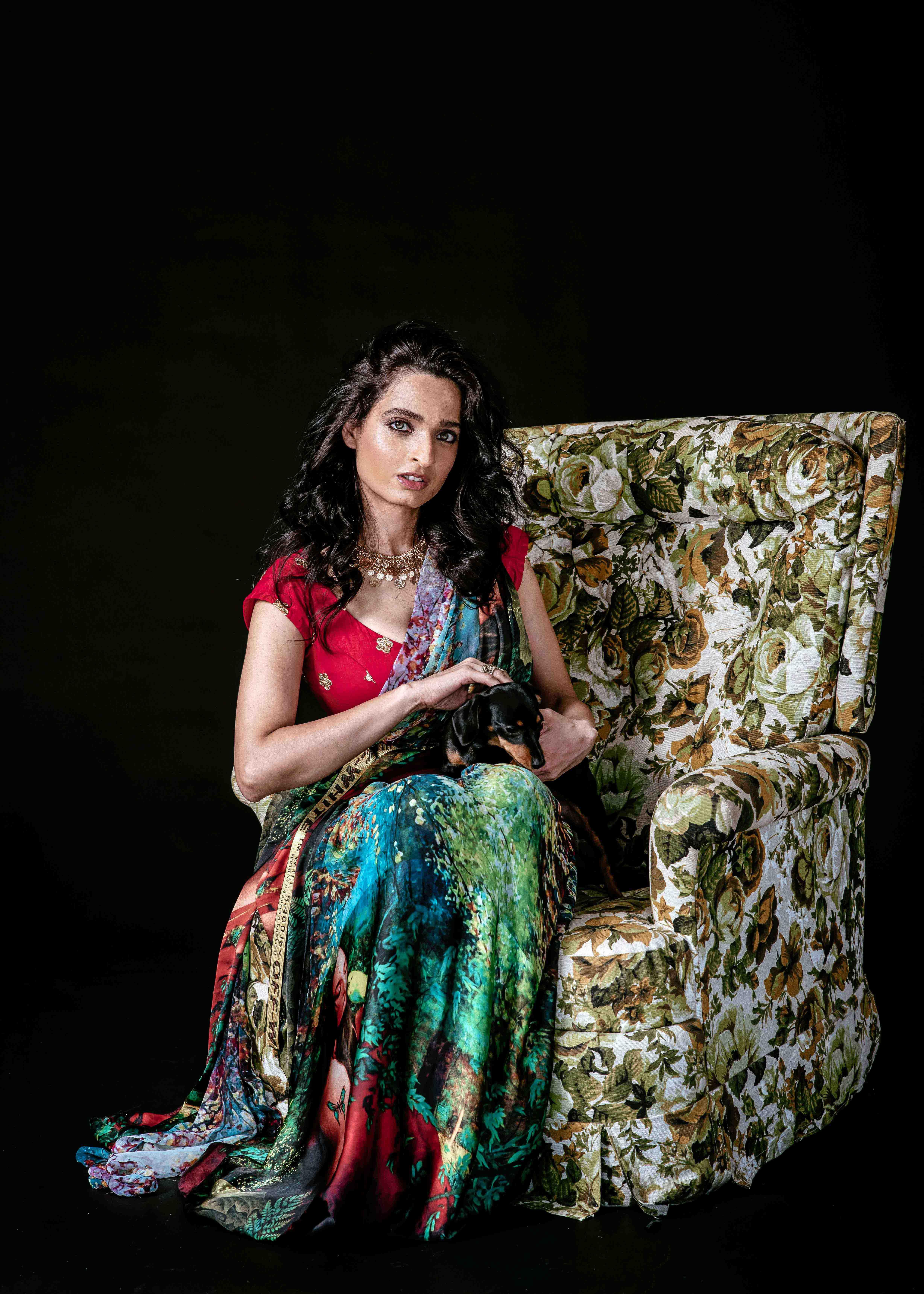 Green Saree sitting on floral chair with daschund sausage dog
