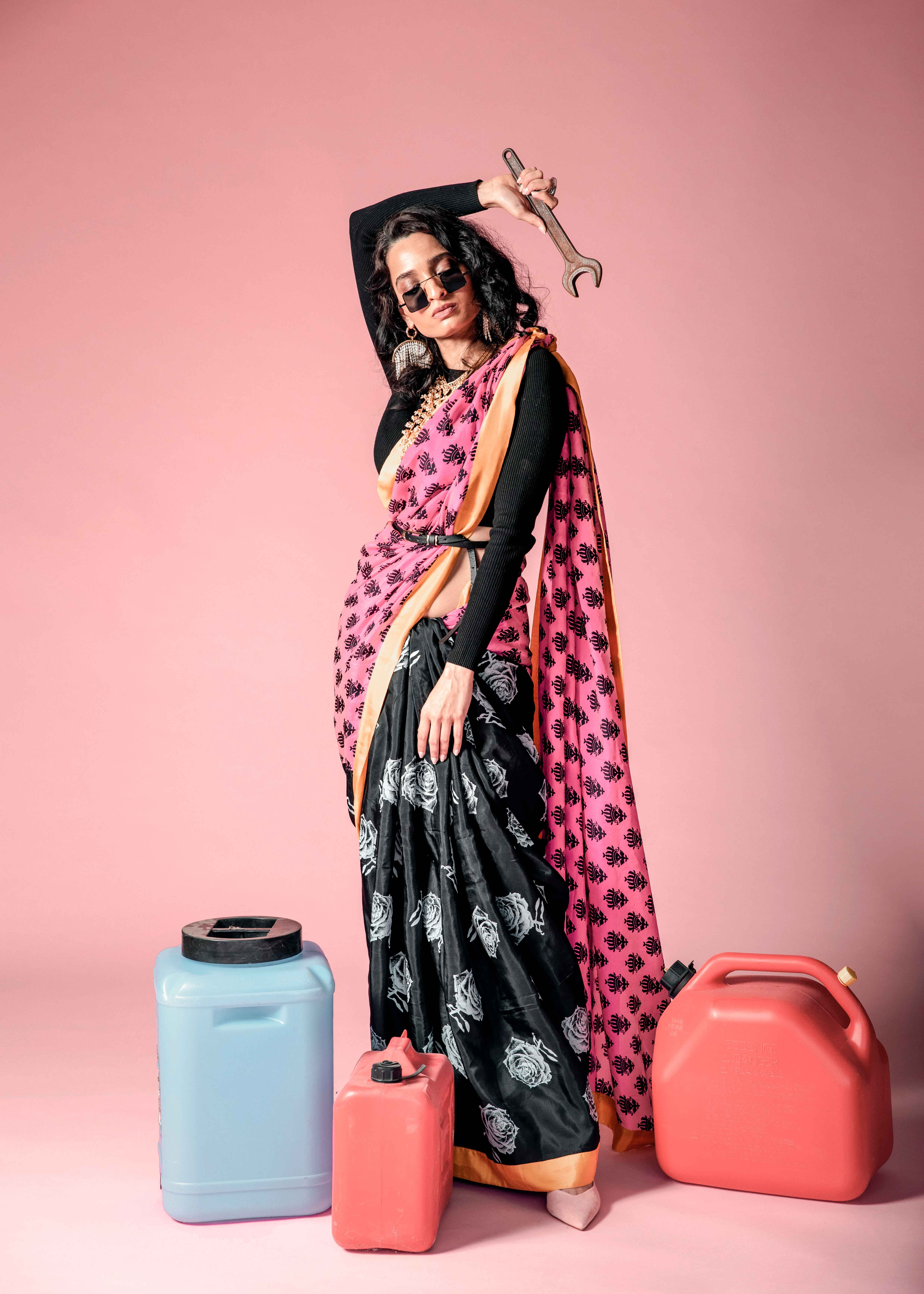 Pink and black designer saree Indian outfit portrait with sunglasses and chandelier peal statement earrings in studio photography with pink background