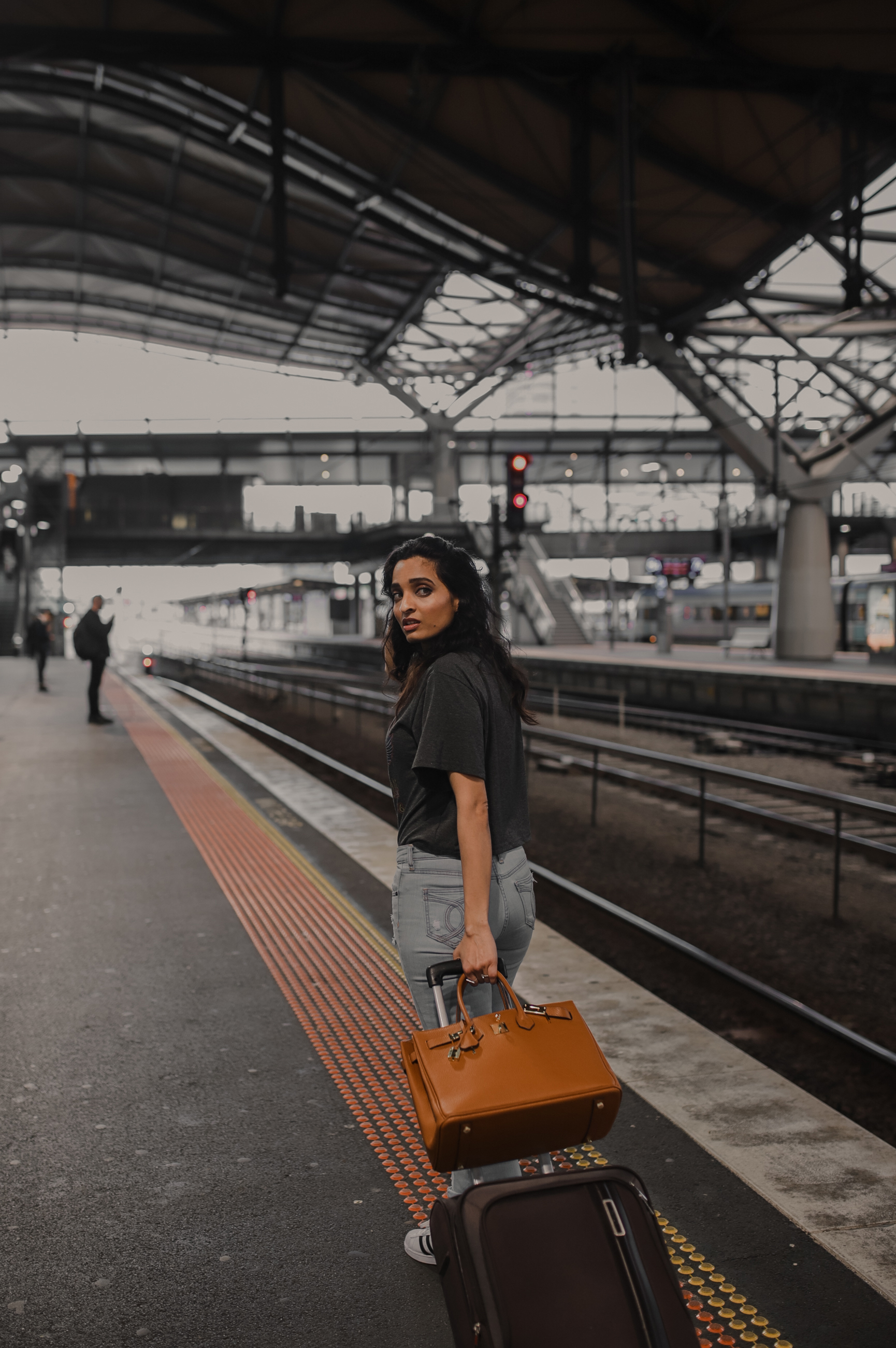 Traveling girl with carry-on luggage and purse at train station wearing blue jeans and grey tee-shirt