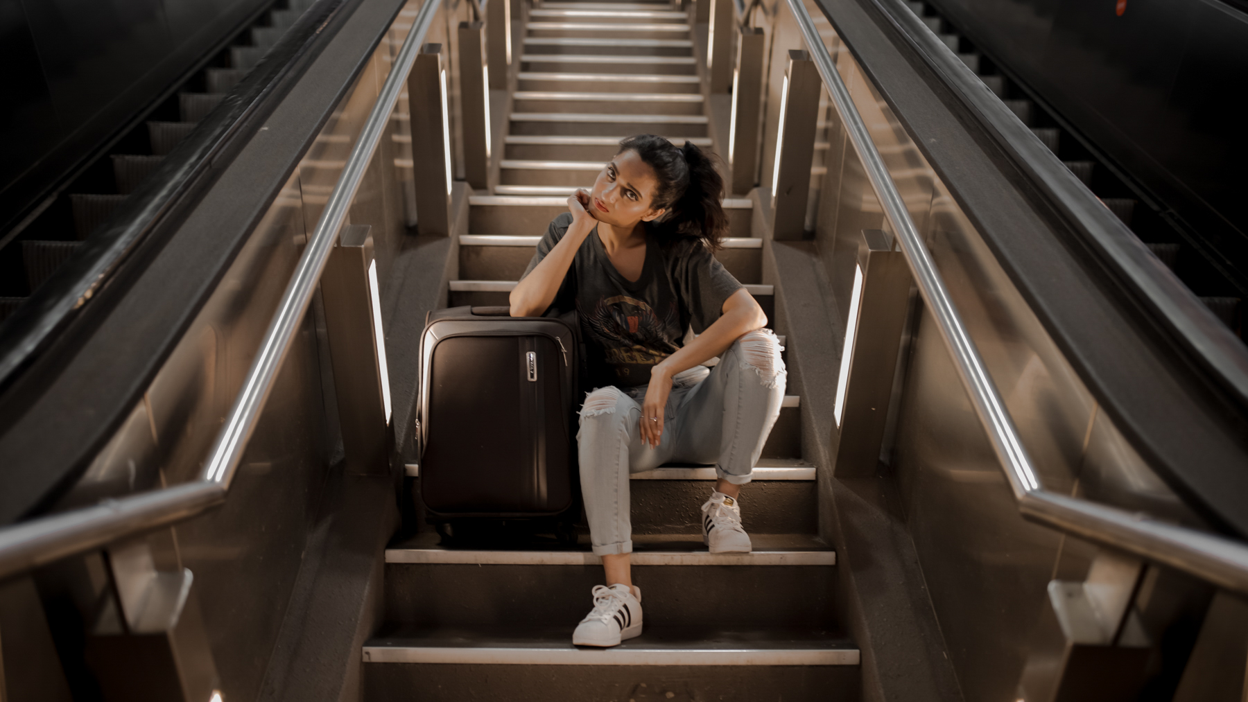 Traveling girl with carry-on luggage sitting on steps wearing jeans and grey tee-shirt and white sneakers