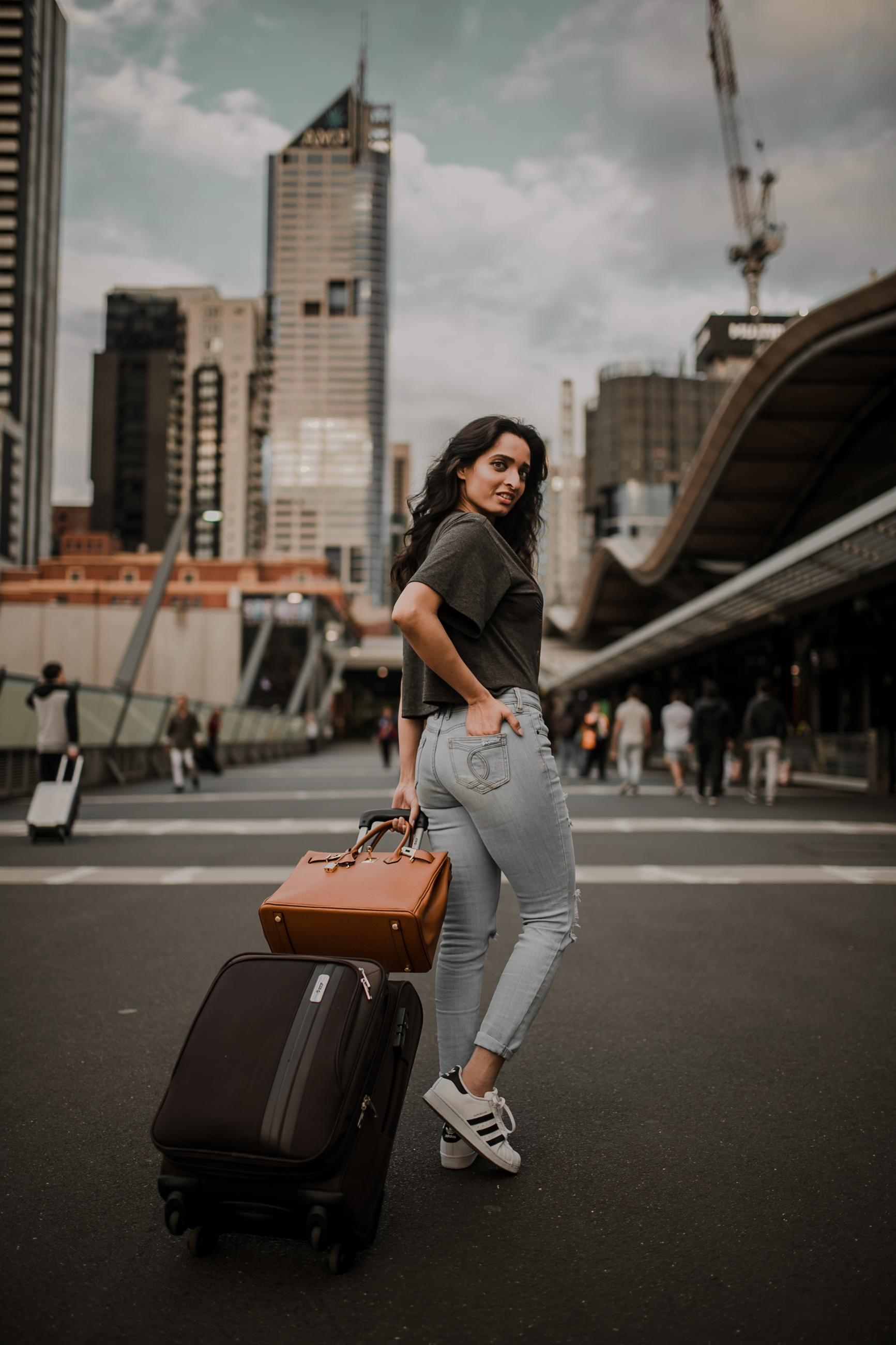 Traveling girl with carry-on luggage and tan purse wearing jeans and grey tee-shirt and white sneakers in the city