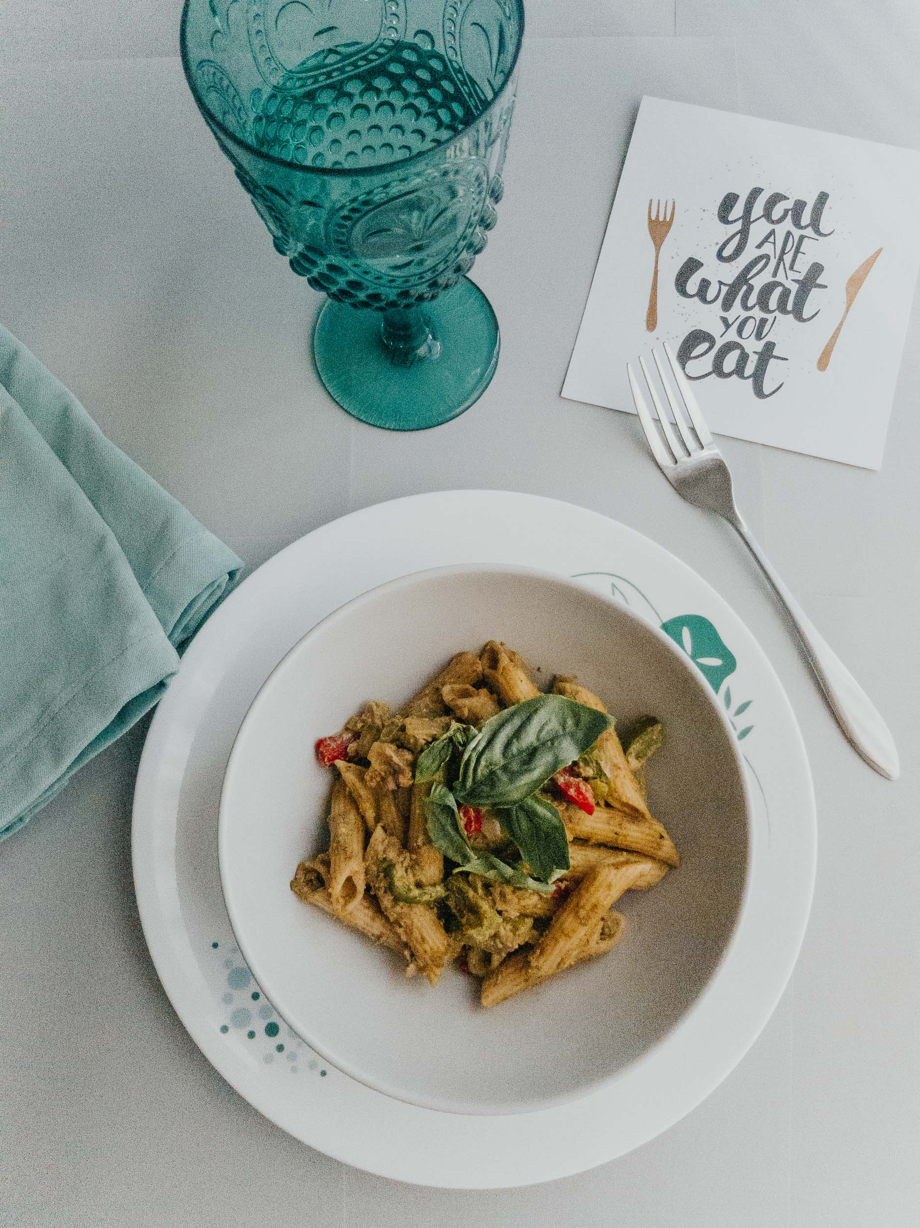 Healthy homemade penne pasta with avocado pesto and blue wine glass