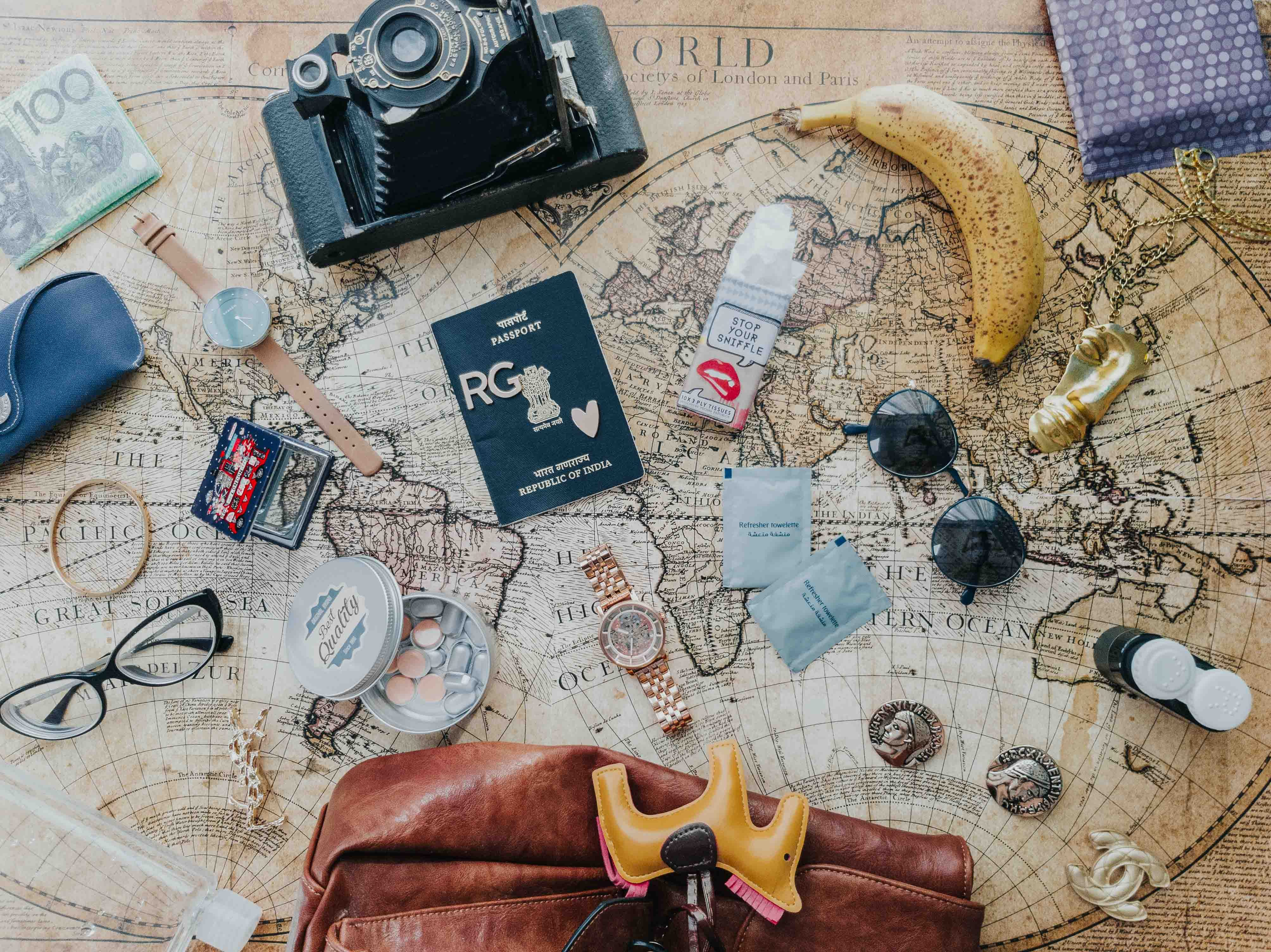 travel packing list items in flatlay a map passport camera water-bottle sunglasses snacks
