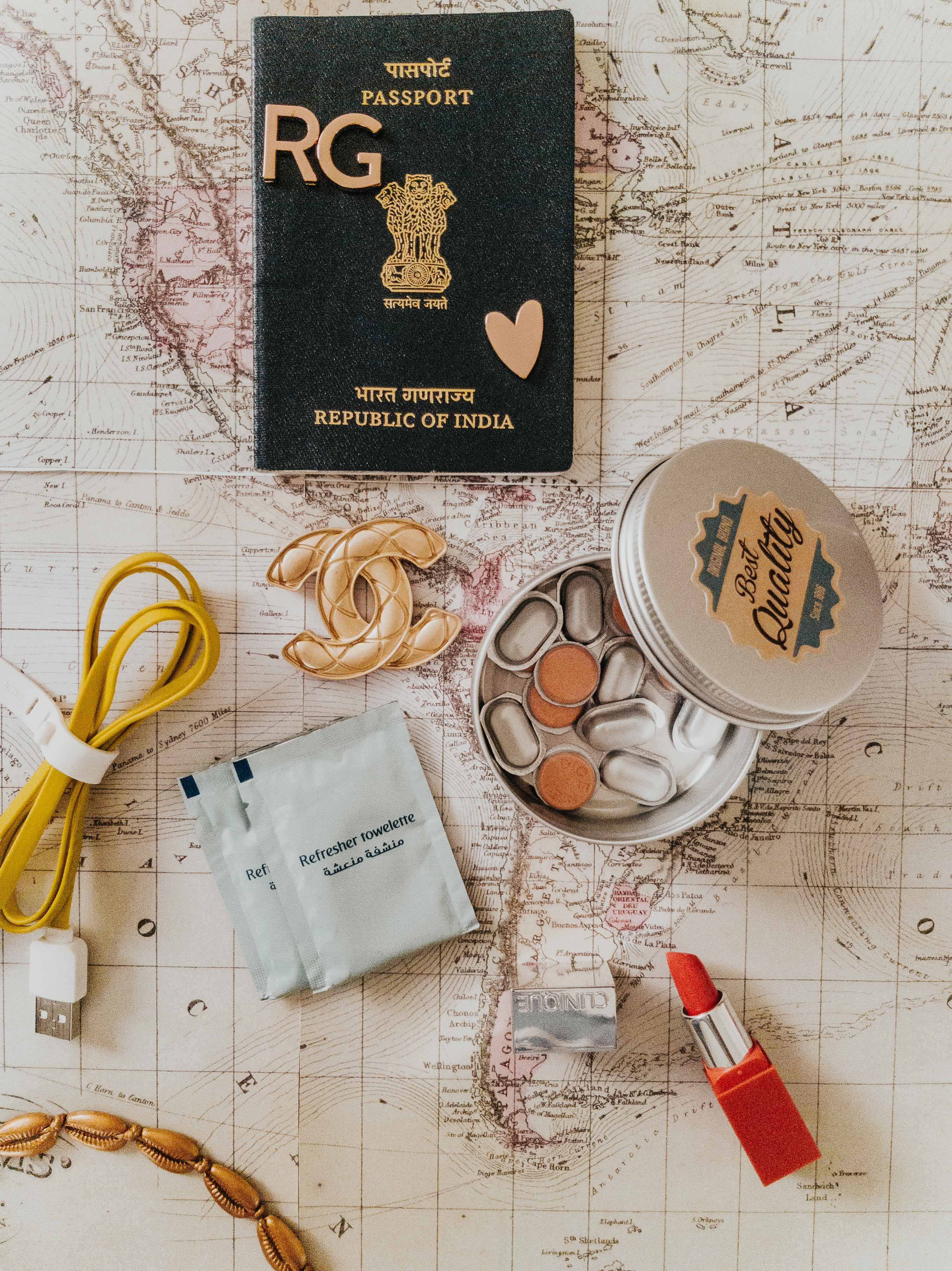 travel packing list items in flatlay a map passport usb cable lipstick medicines