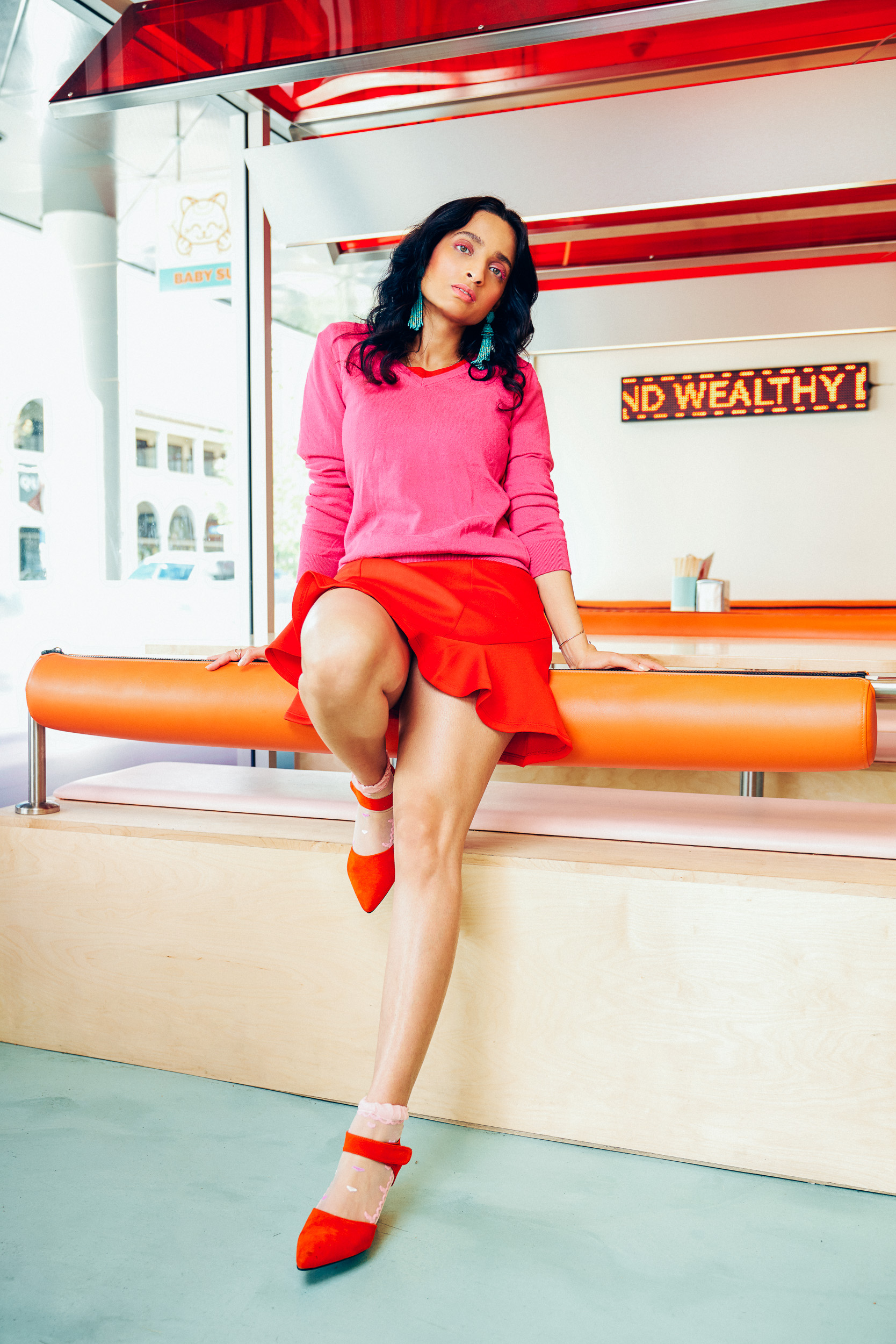Girl posing in restaurant with pastel interiors wearing red dress and pink sweater outfit. Illustrative image for to discuss what i wish my younger self knew
