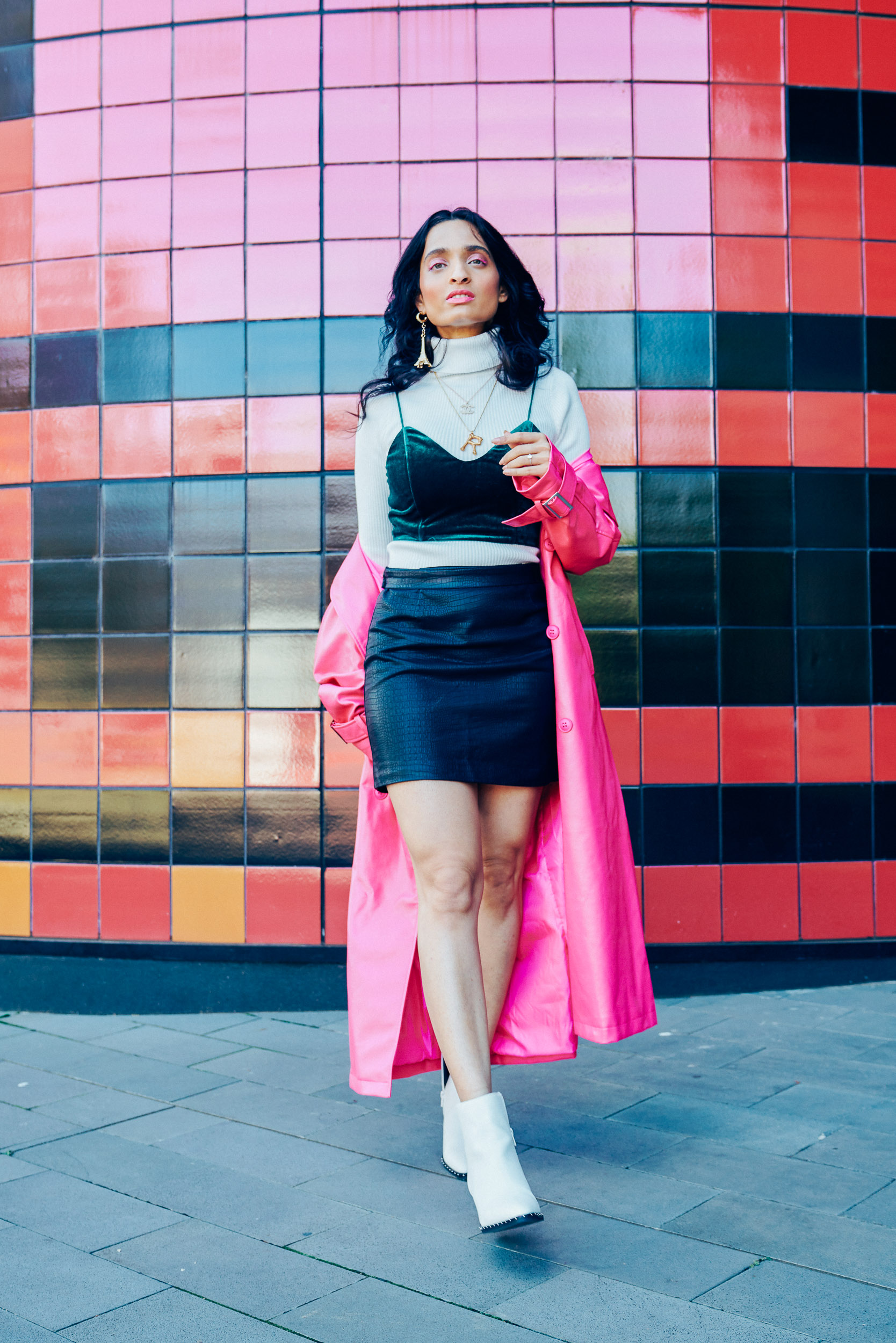 Girl wearing autumn outfit including black leather skirt with white sweater, green velvet camisole crop top, white boots and hot pink pleather jacket. Illustrative image for to discuss what i wish my younger self knew