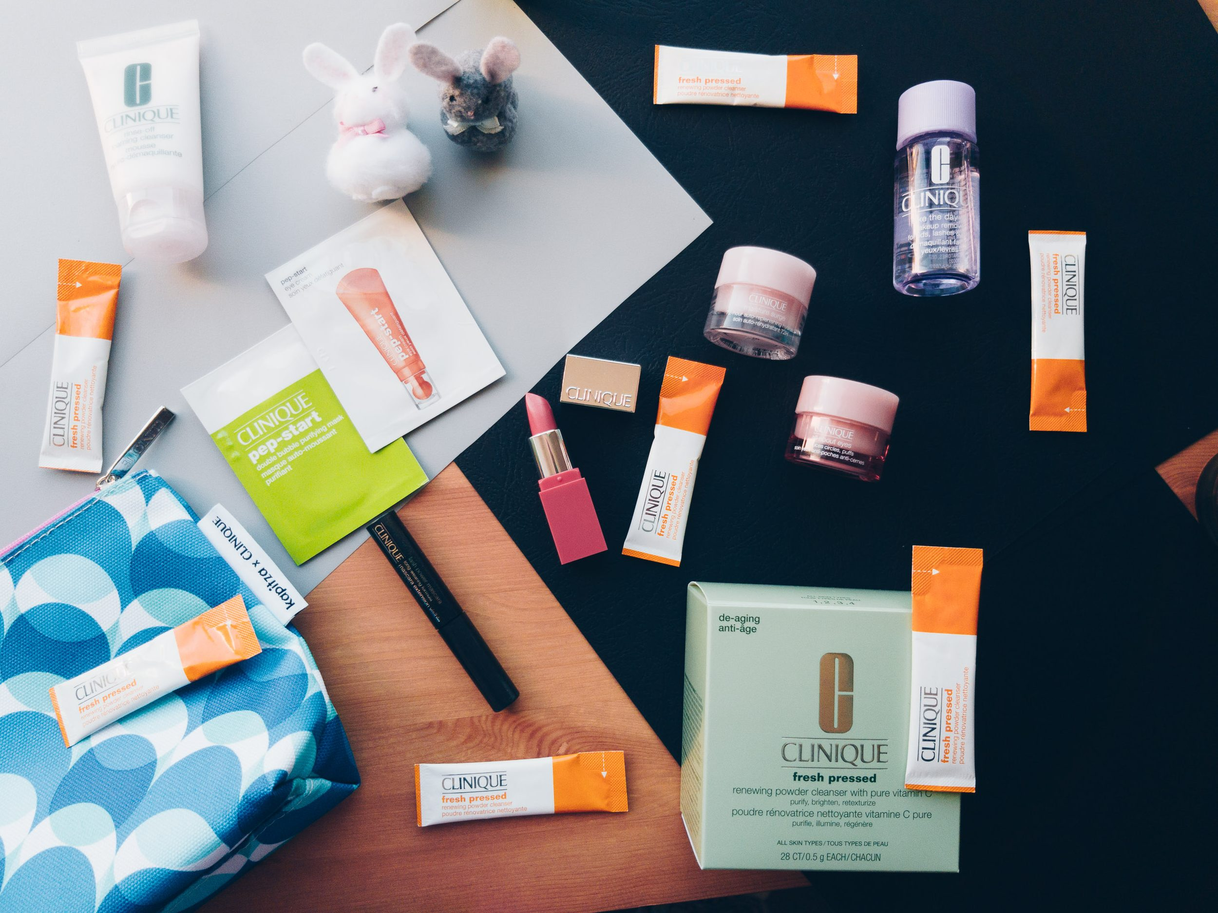 Clinique Fresh Pressed™ Renewing Powder Cleanser with Pure Vitamin C review with flatlay of sachets of the product and other clinique beauty products in orange and white