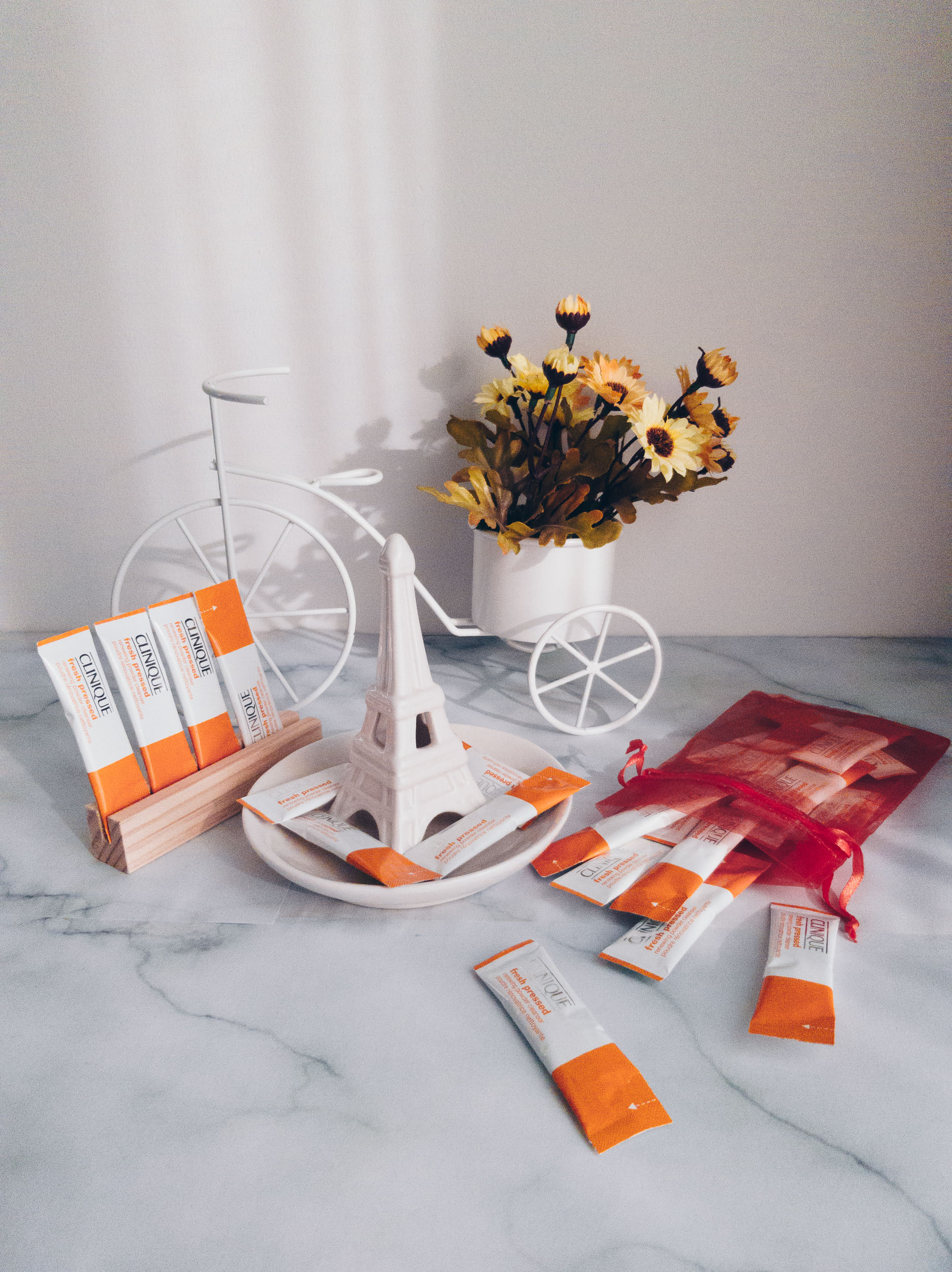 Clinique Fresh Pressed™ Renewing Powder Cleanser with Pure Vitamin C review with flatlay of sachets of the product in orange and white
