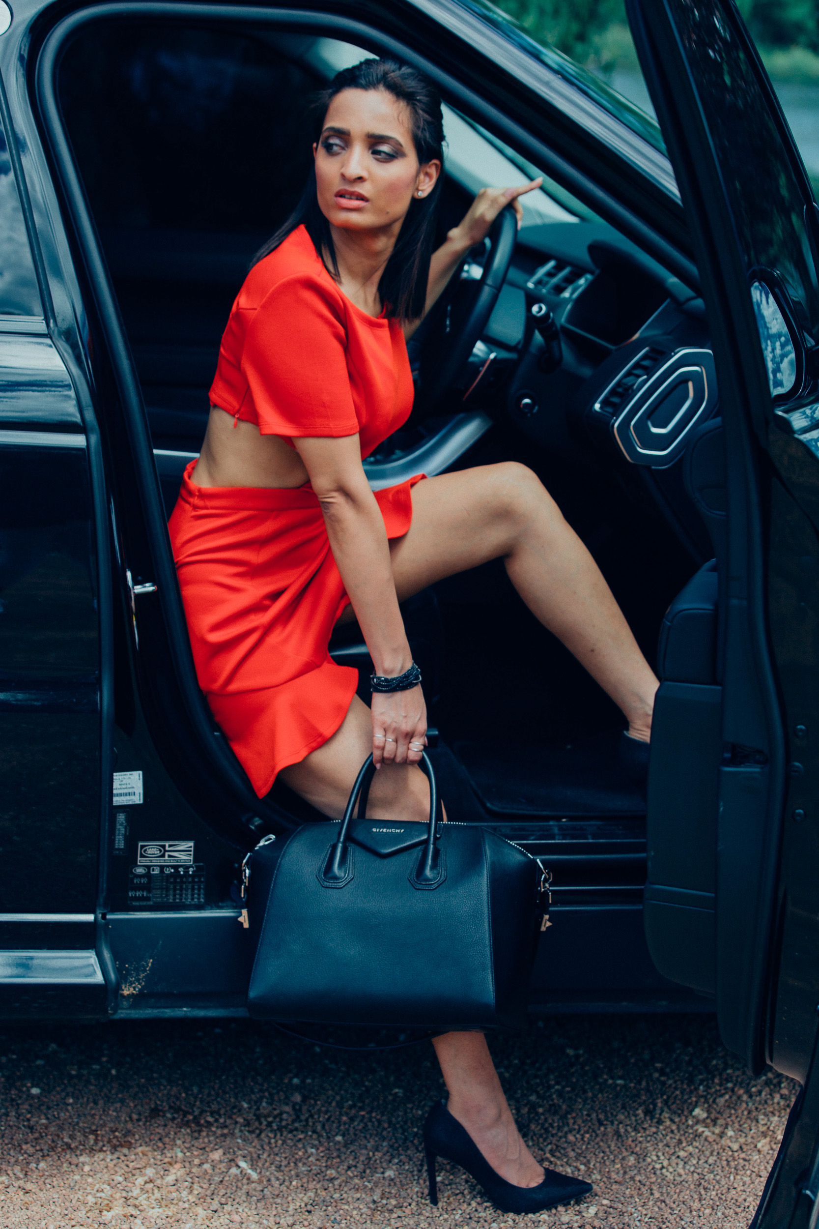 Girl wearing red dress holding a Givenchy purse posing with a land rover car
