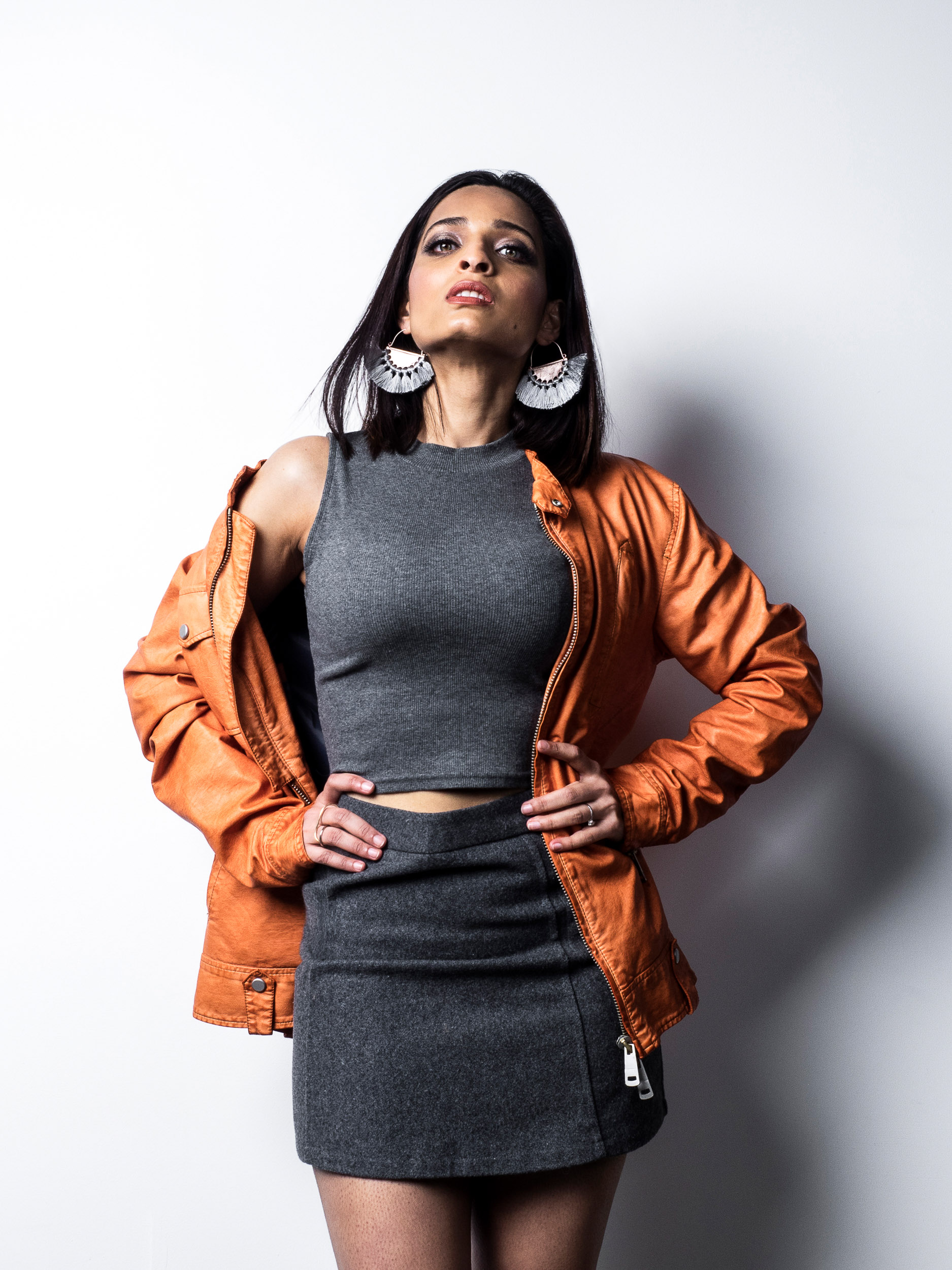 Studio photo of girl in short hair wearing gray matching skirt and top with orange leather jacket.