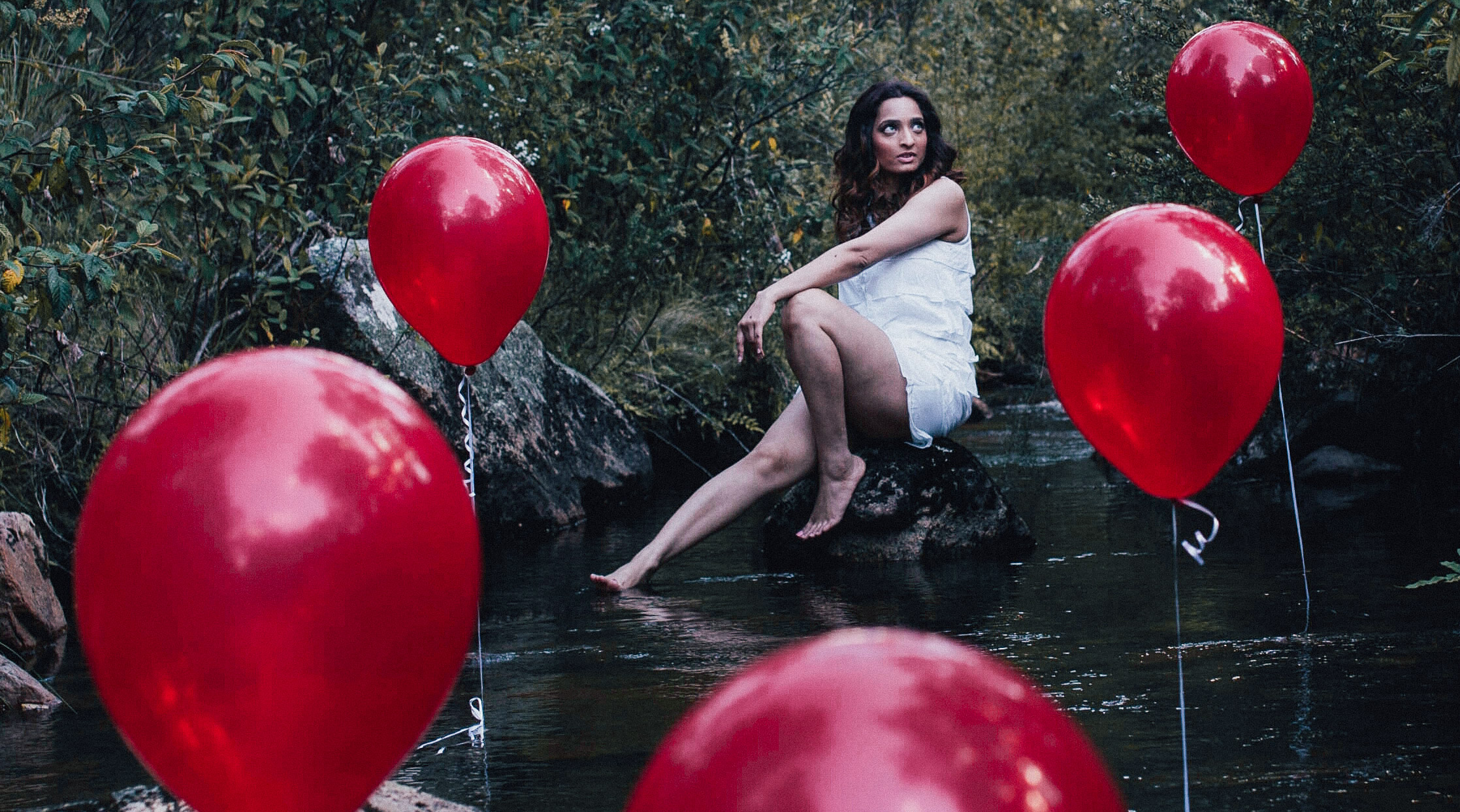 Girl in white dress sitting on a stone in a river with red balloons in the river around her