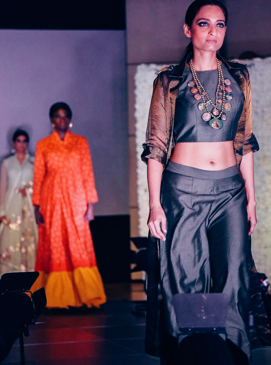 Girl walking down the runway wearing indo-western outfit of golden-green crop top and palazzo pants along with a statement necklace