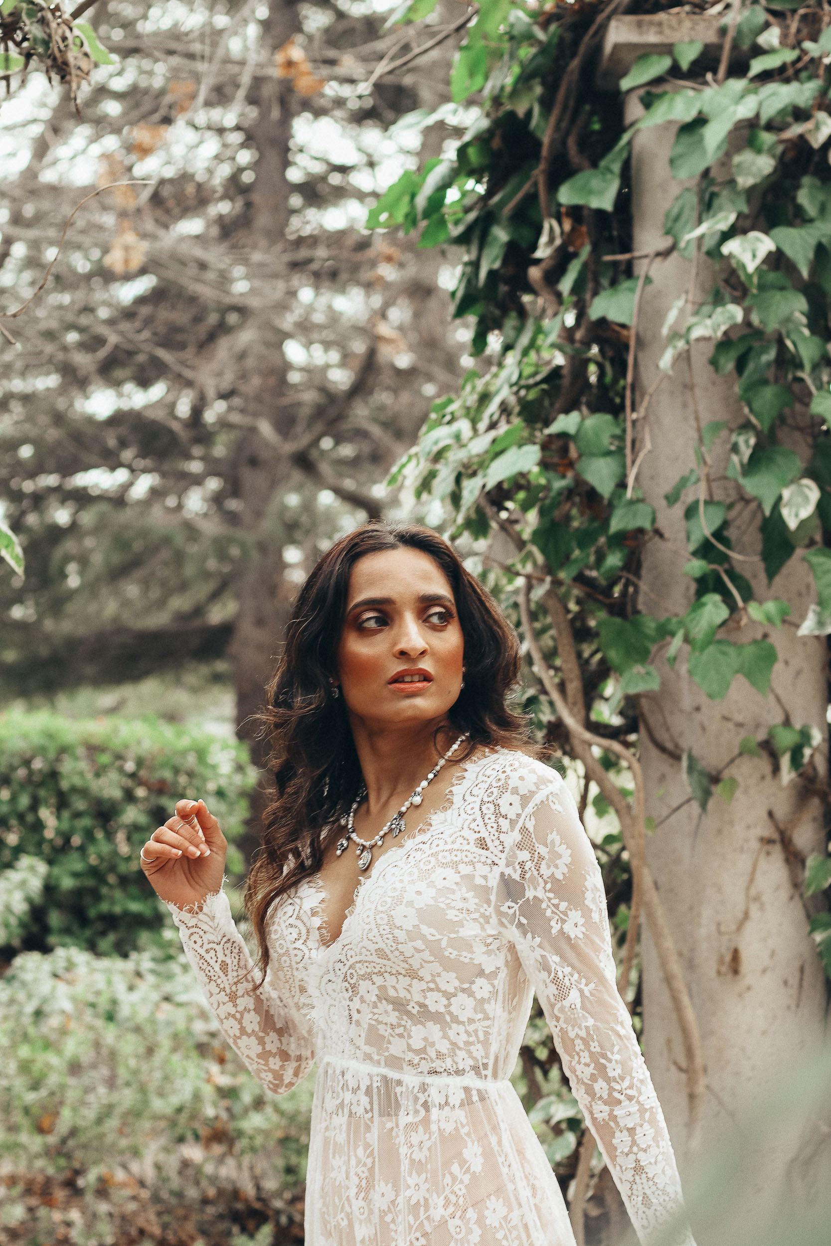 Girl standing in forest wearing white lace gown, moody shot-to discuss PMS and mental health