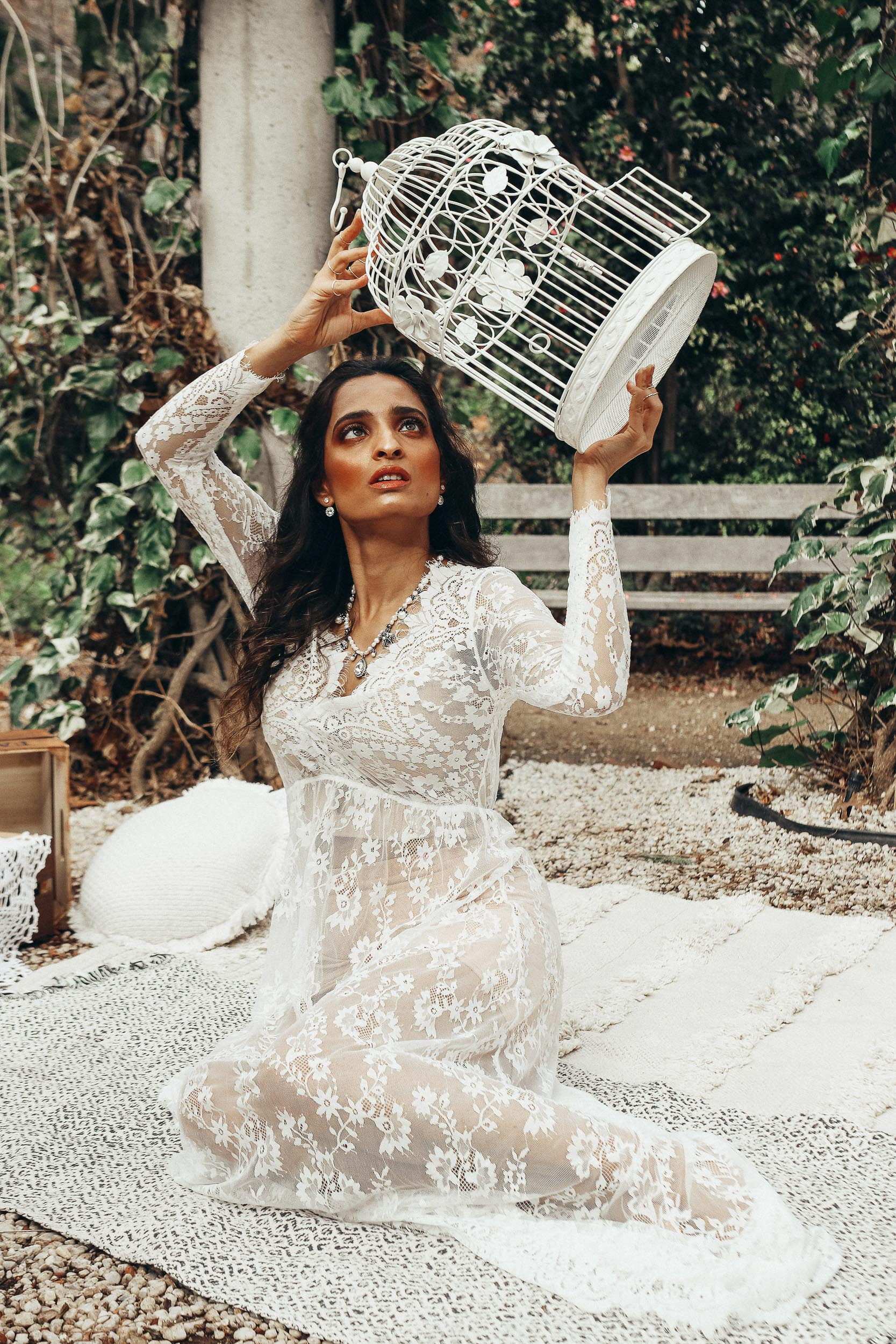 Girl sitting on a mat in forest wearing white lace gown and holding a white bird cage prop, moody shot-to discuss PMS and mental health
