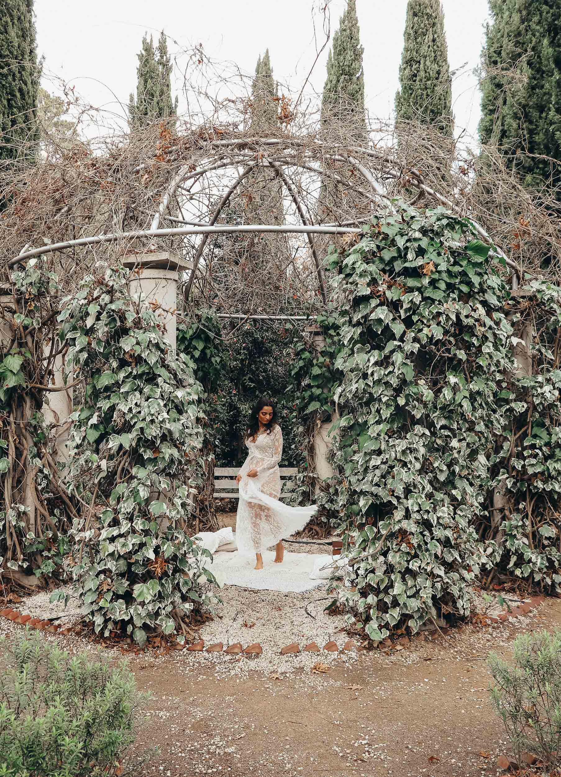 Girl standing on a mat in forest wearing white lace gown and twirling her grown for moody shot-to discuss PMS and mental health