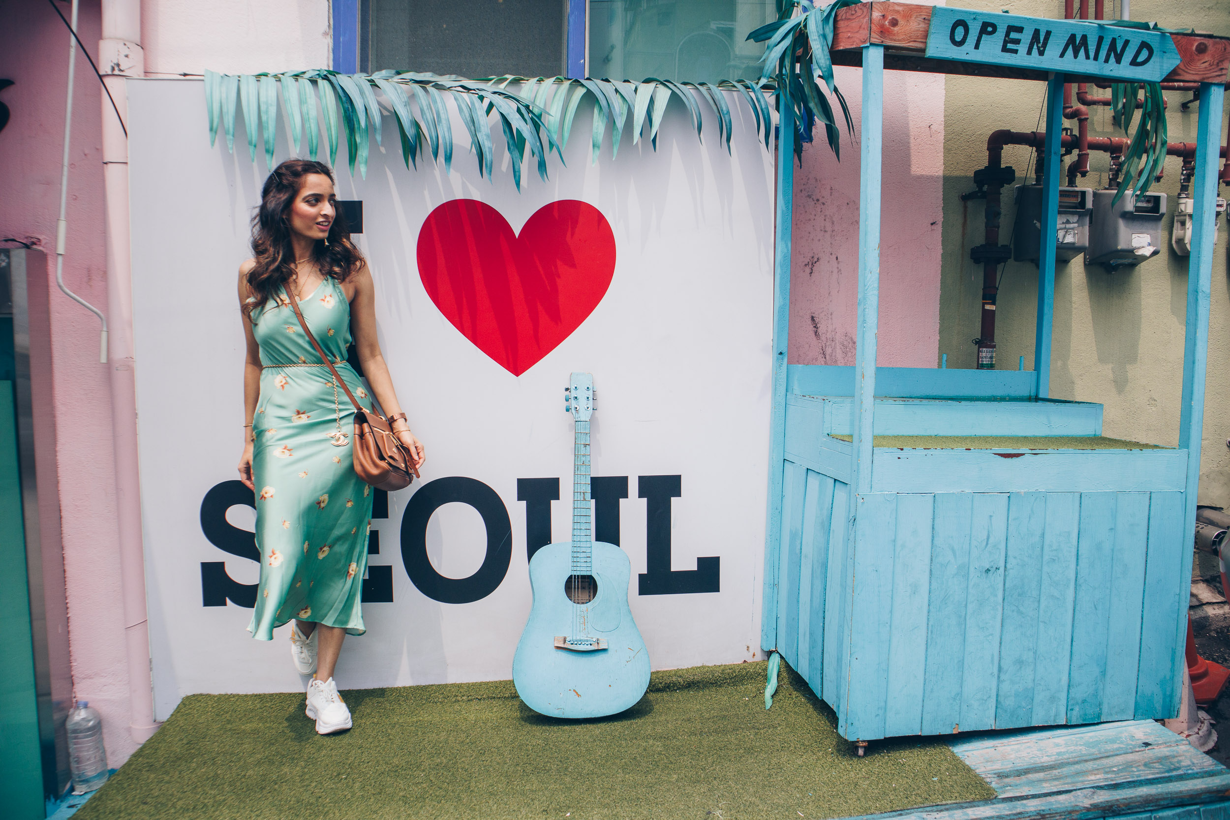 Girl traveller standing against the wall with caption reading I heart Seoul, wearing green slip dress and white sneakers