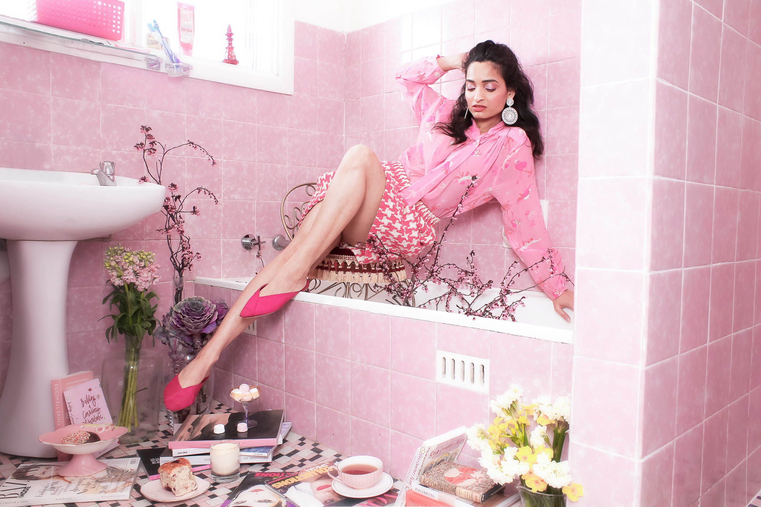 Creative editorial in a pink bathroom with the girl sitting in bathtub wearing pink outfit