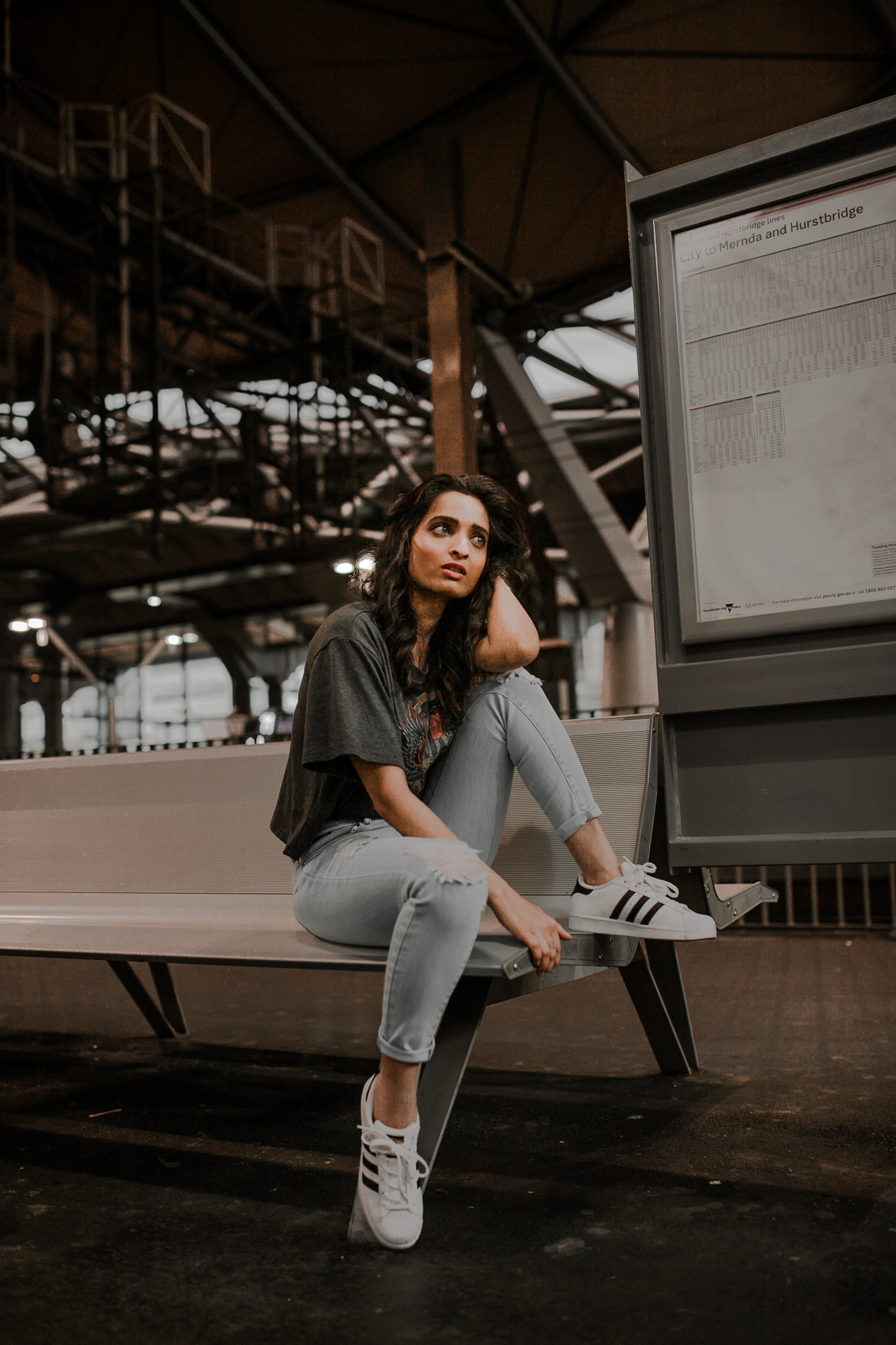 Girl sitting on bench wearing casual jeans and tee-shirt outfit with sneakers at a train station in Melbourne