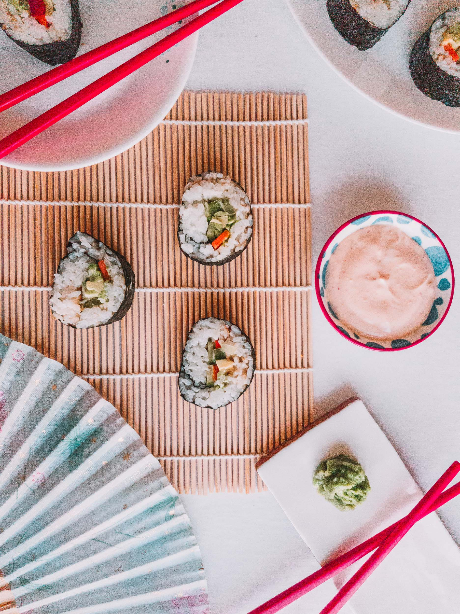 flatlay of vegetarian shushi rolls on sushi rolling mat with spicy sauce