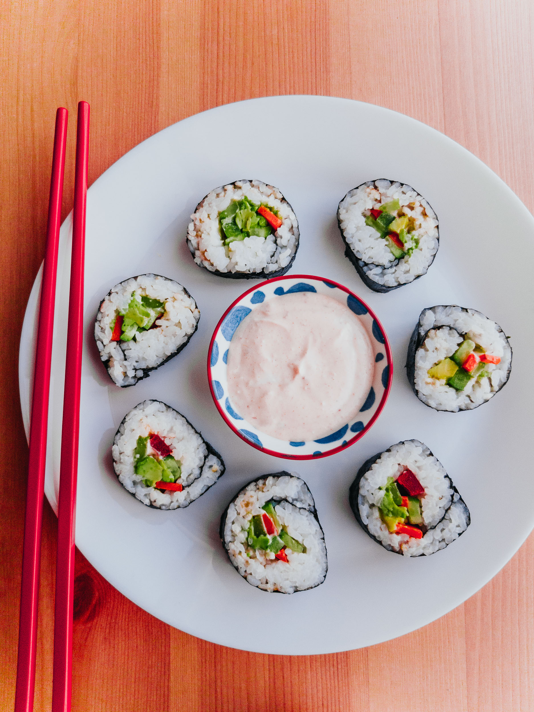 flatlay of vegetarian shushi rolls with red chopsticks