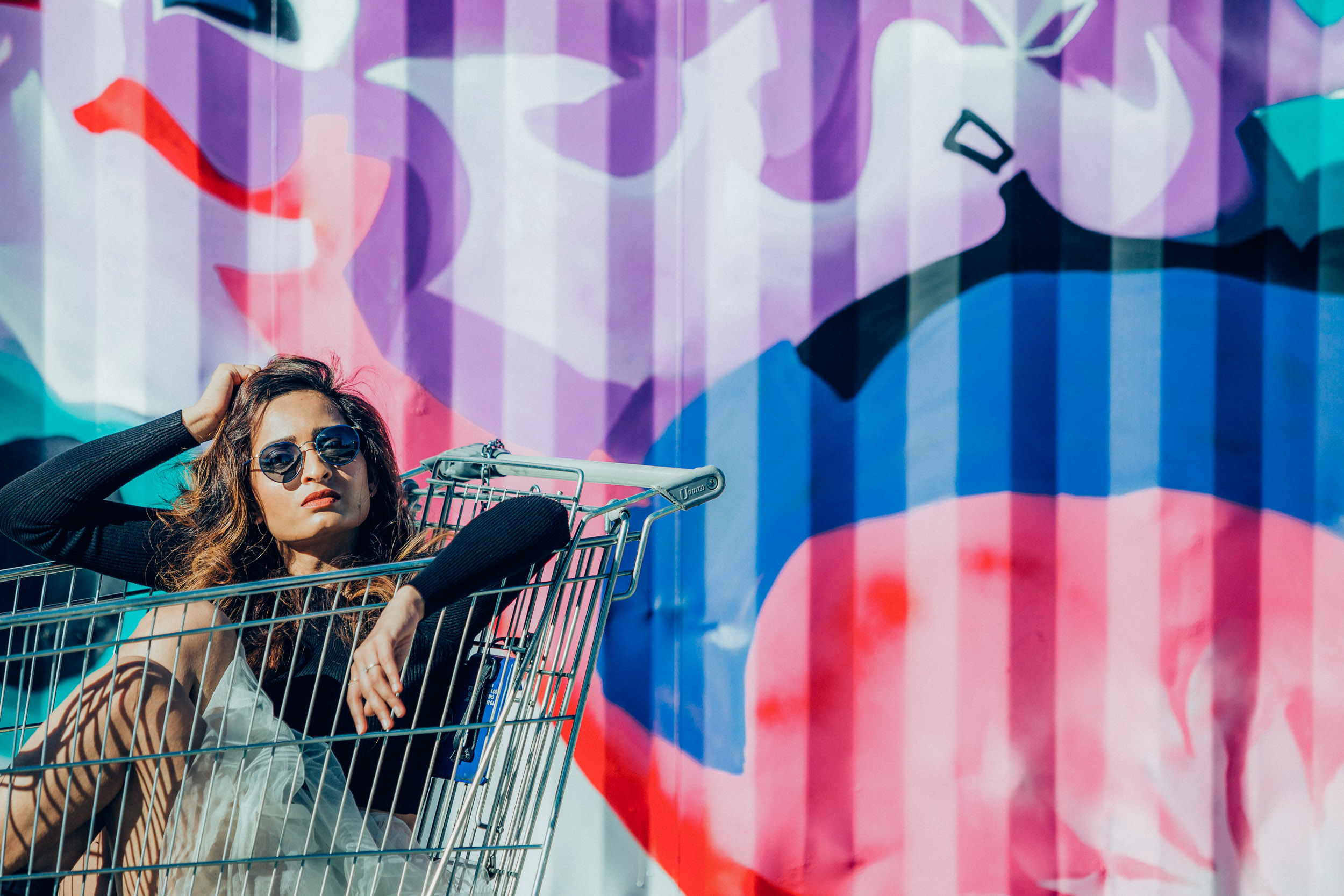 Girl wearing black sweater and sitting in a shopping cart in front of graffiti wall
