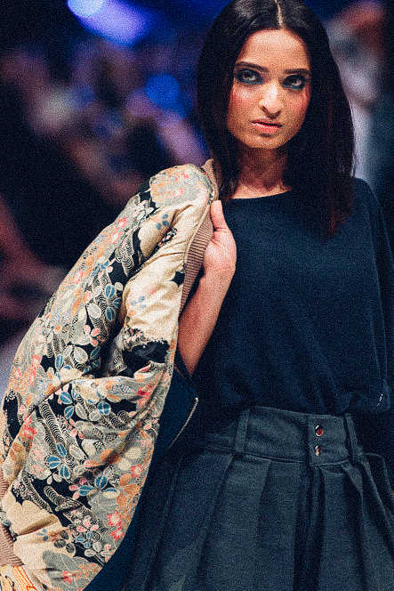 Runway photo of girl wearing dark blue tee-shirt and colourful patterned puffer jacket and thick pleated gray pants