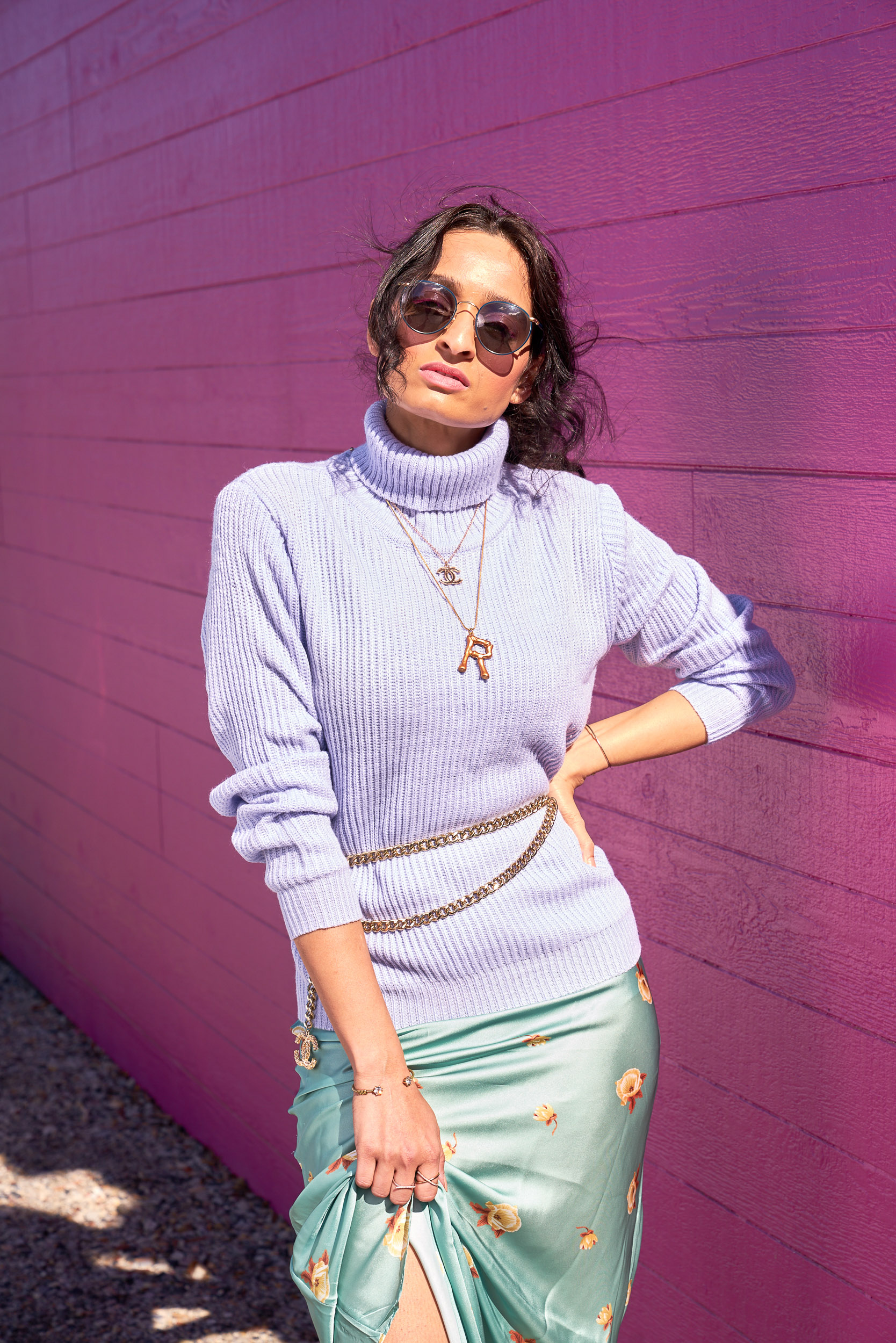 girl wearing lavender sweater and teal silk dress against pink wall