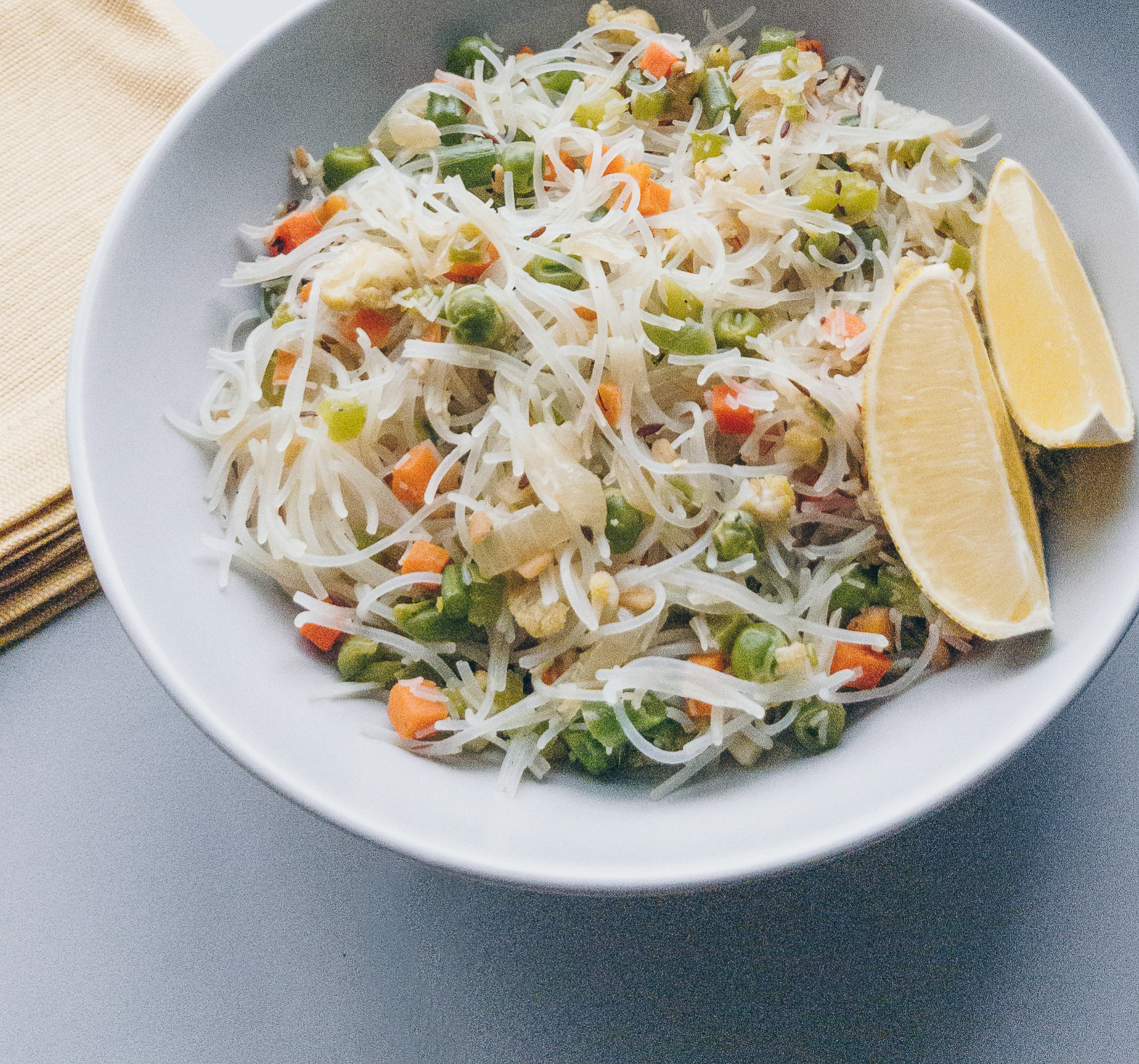 close up of vermicelli with vegetables and lemon on the side