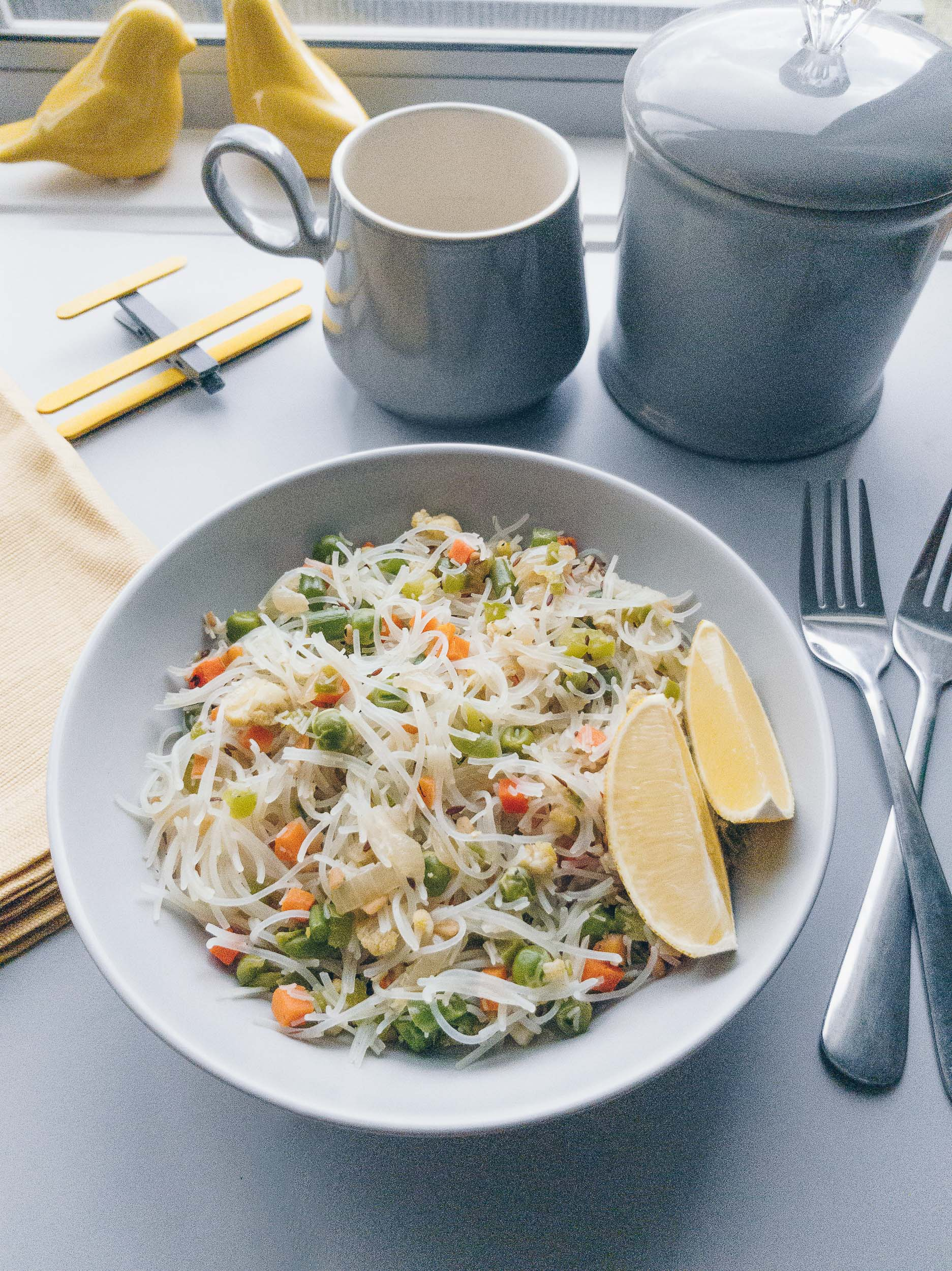 table flatlay of vermicelli with vegetables and lemon on the side and tea-cup alongside