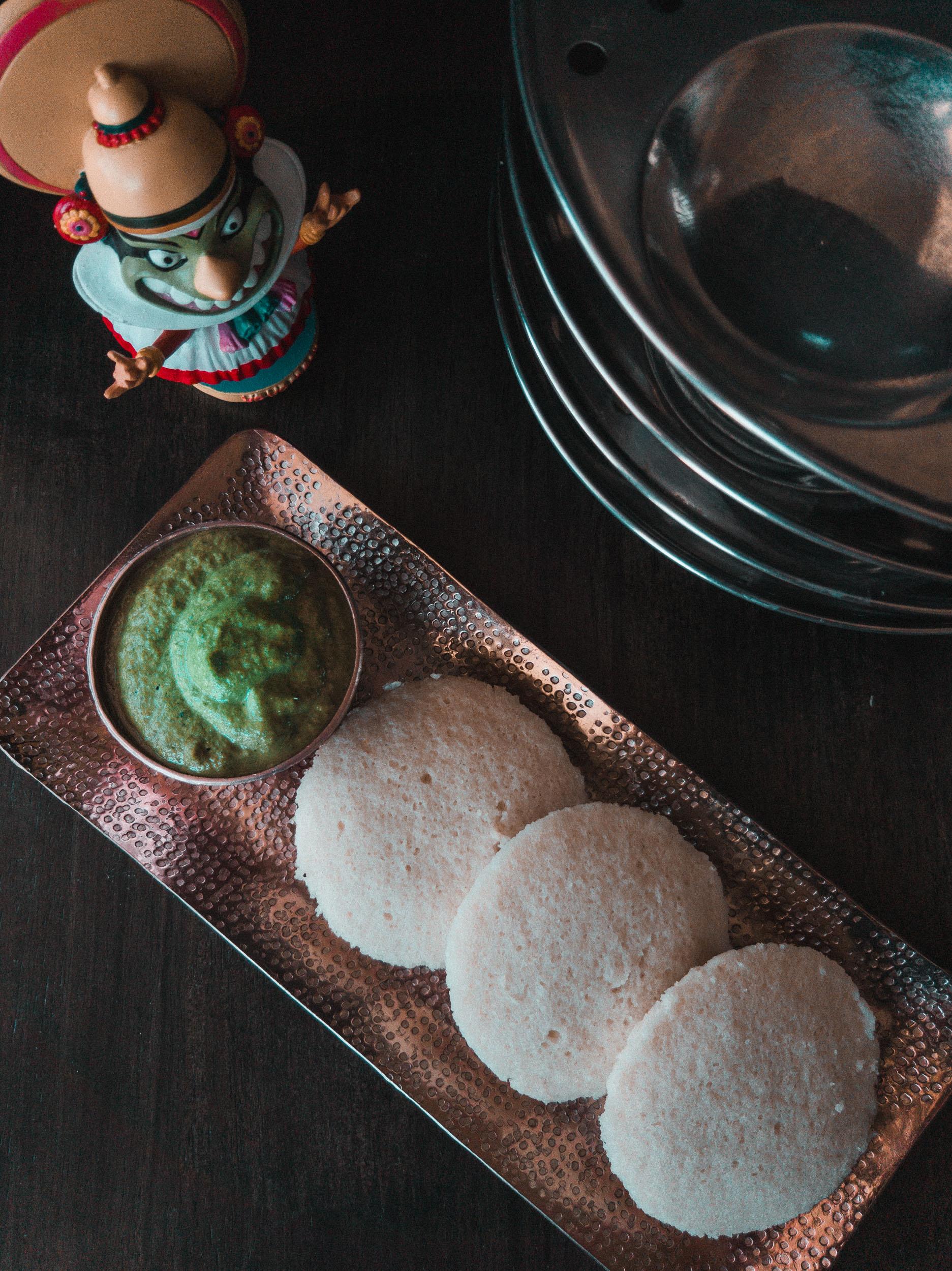 Flatlay of idli with green peanut coconut coriander chutney alongside an idli stand and kathakali dancer boblehead