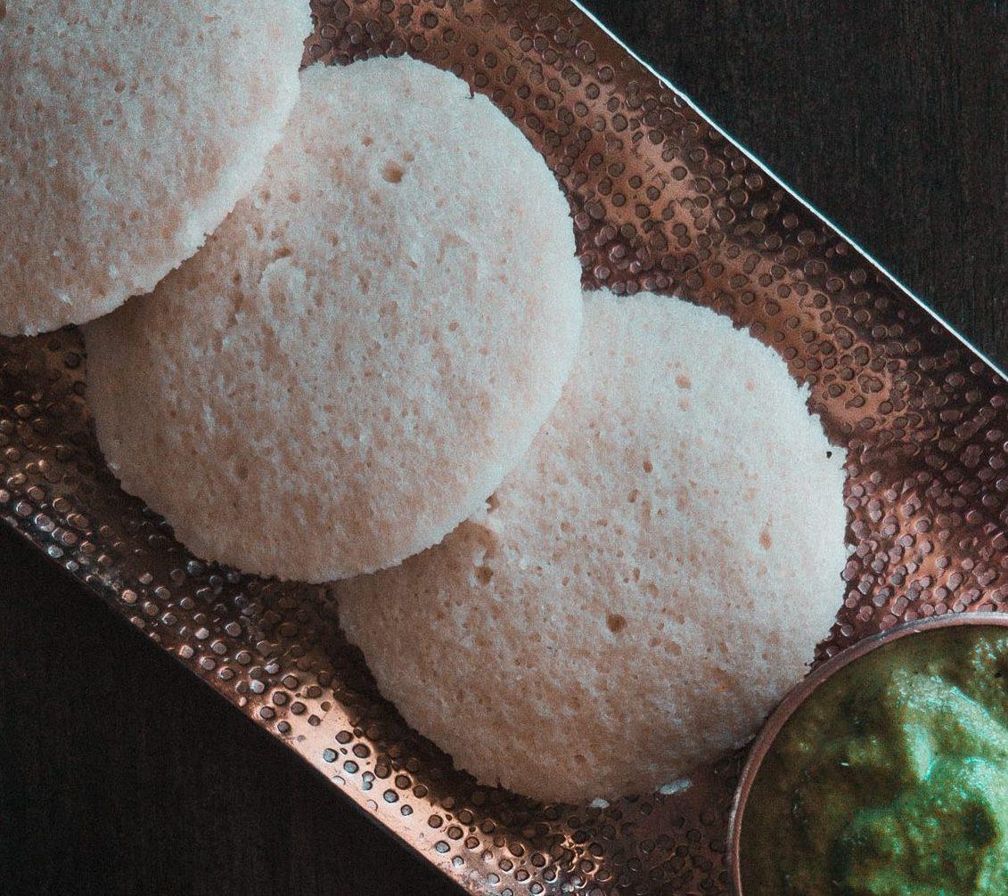 Flatlay of idli with green peanut coconut coriander chutney alongside an idli stand and kathakali dancer boblehead Idli recipe: easy and fuss-free